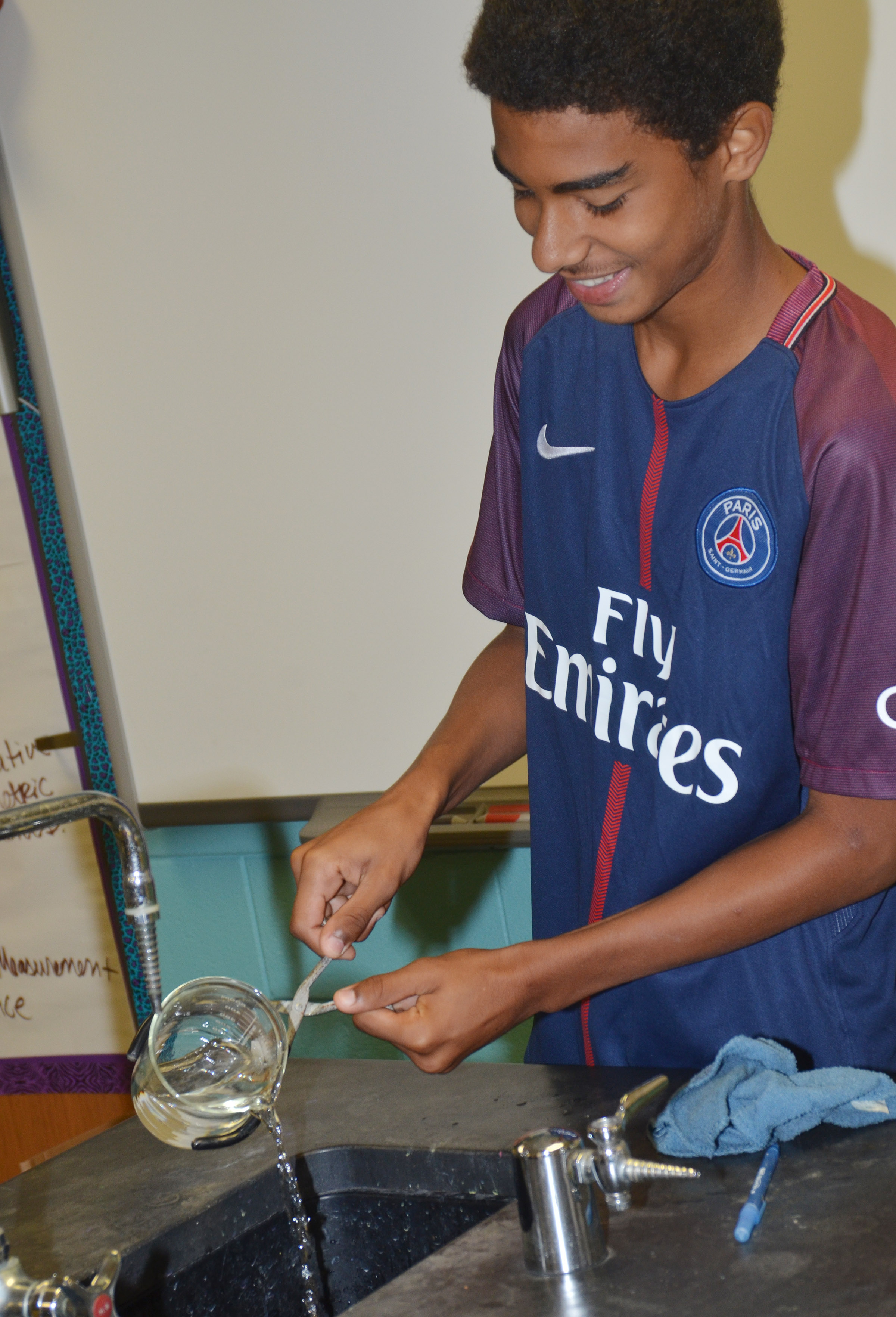 CHS sophomore David Silva pours water as he and his groupmates prepare for their experiment.