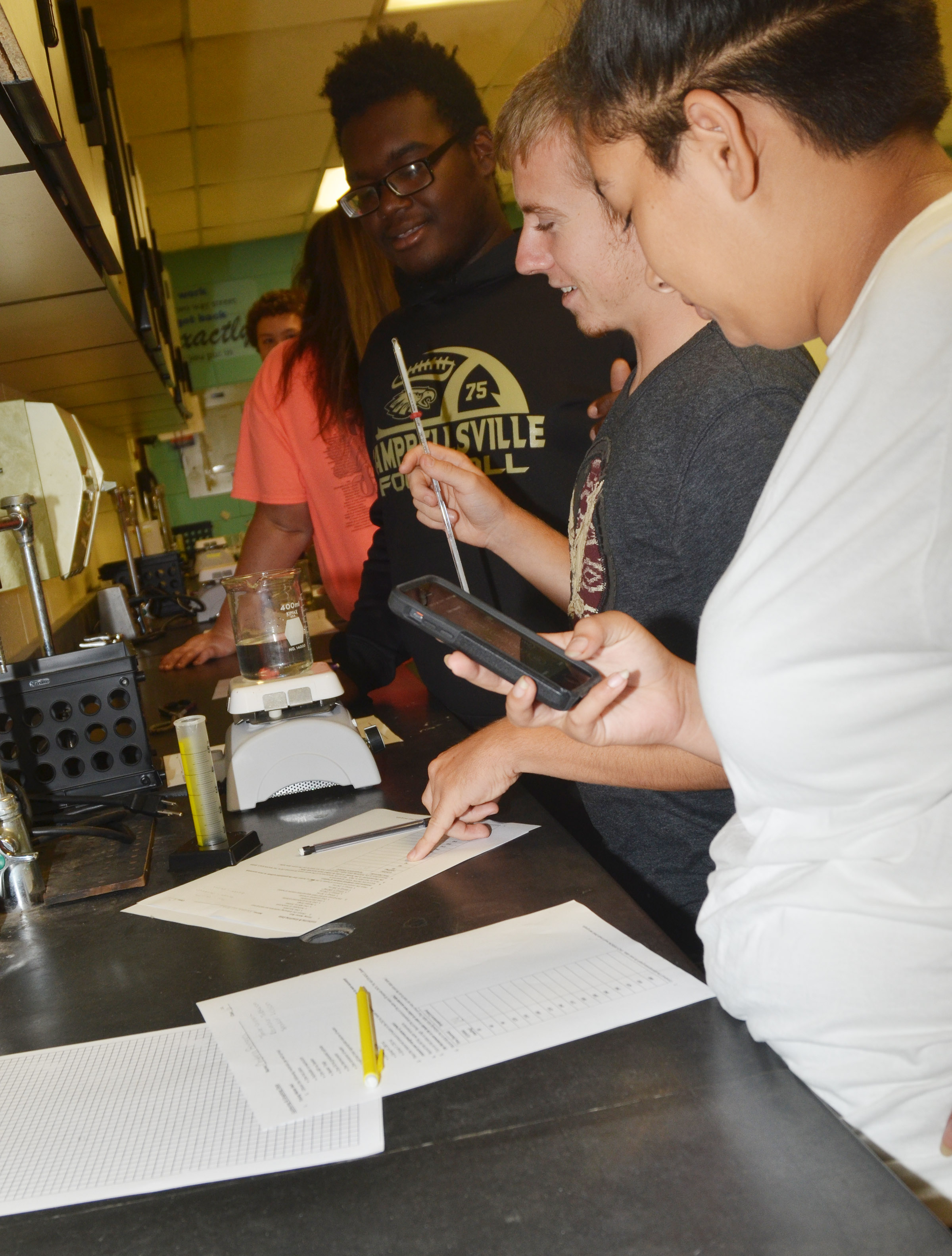 From left, CHS sophomores Taekwon McCoy, Michael Griffiths and Cristina Barrera record the temperature of their water.