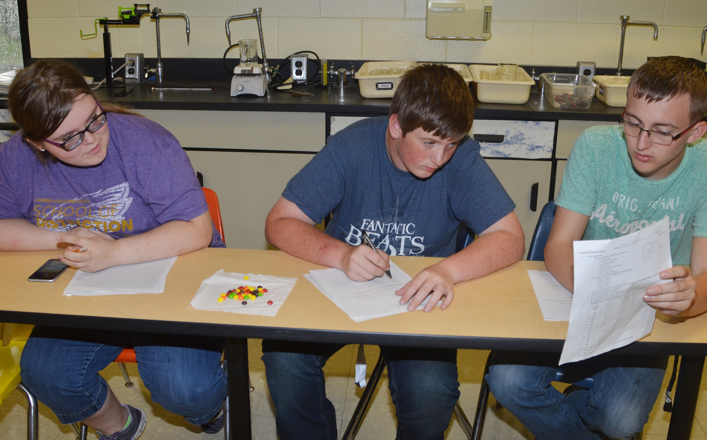 From left, CHS sophomore Taylor Brewer and juniors Quentin Skaggs and Josh Mahan work on creating their graph of water temperatures.