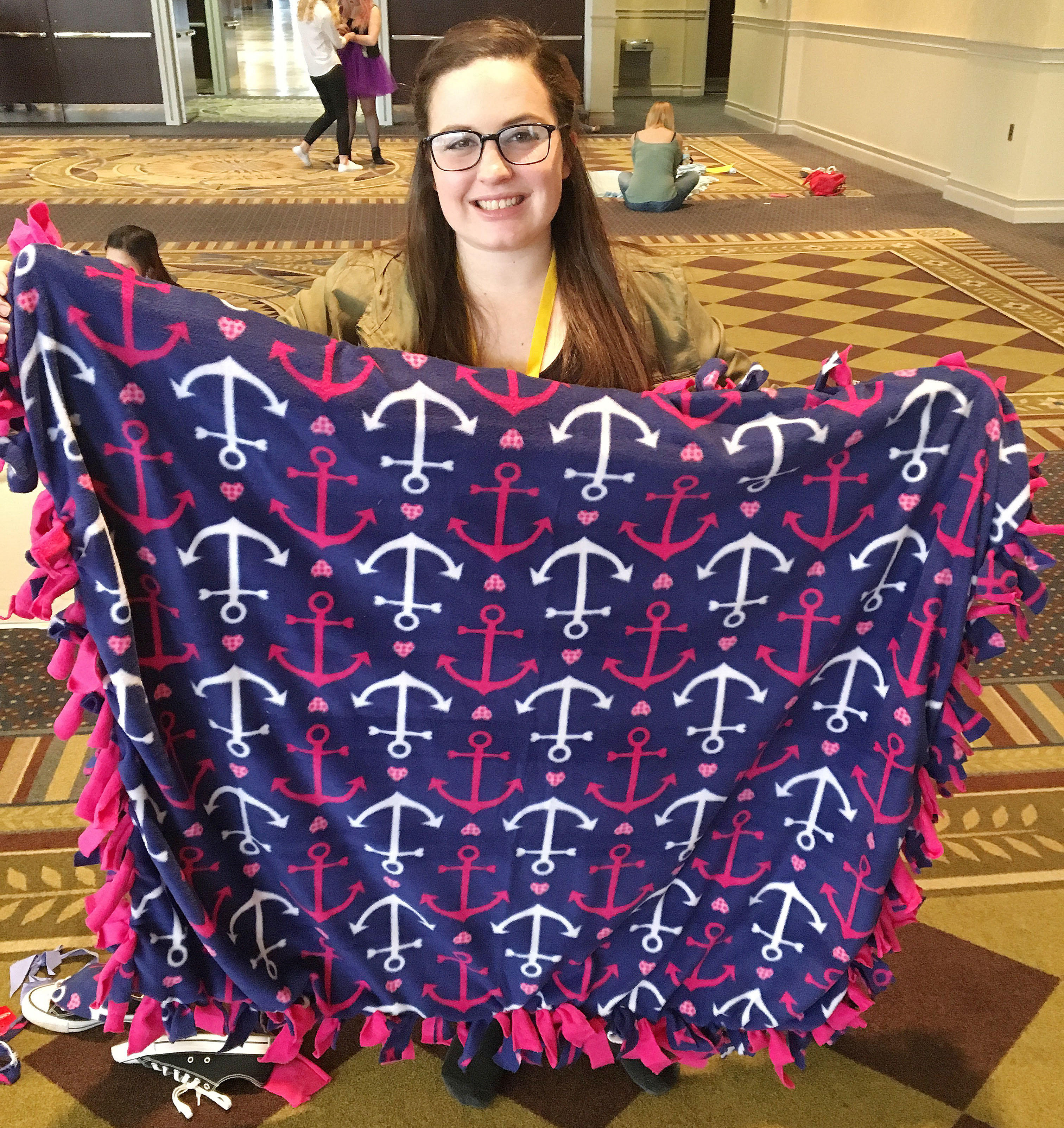 CHS junior Caitlin Bright holds a blanket she made as part of a service project for children.