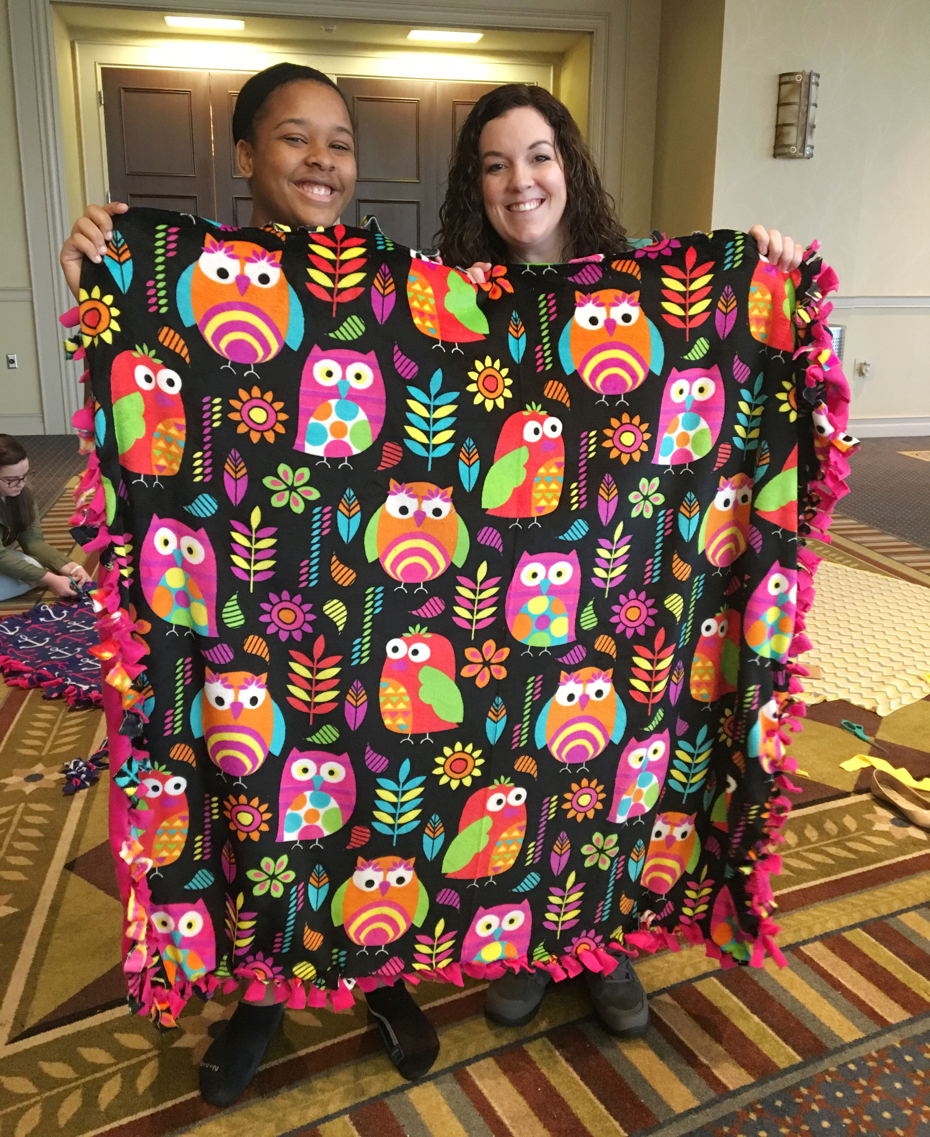 CHS junior Kayla Young, at left, and Beta sponsor Lindsay Williams hold a blanket they made as part of a service project for children.