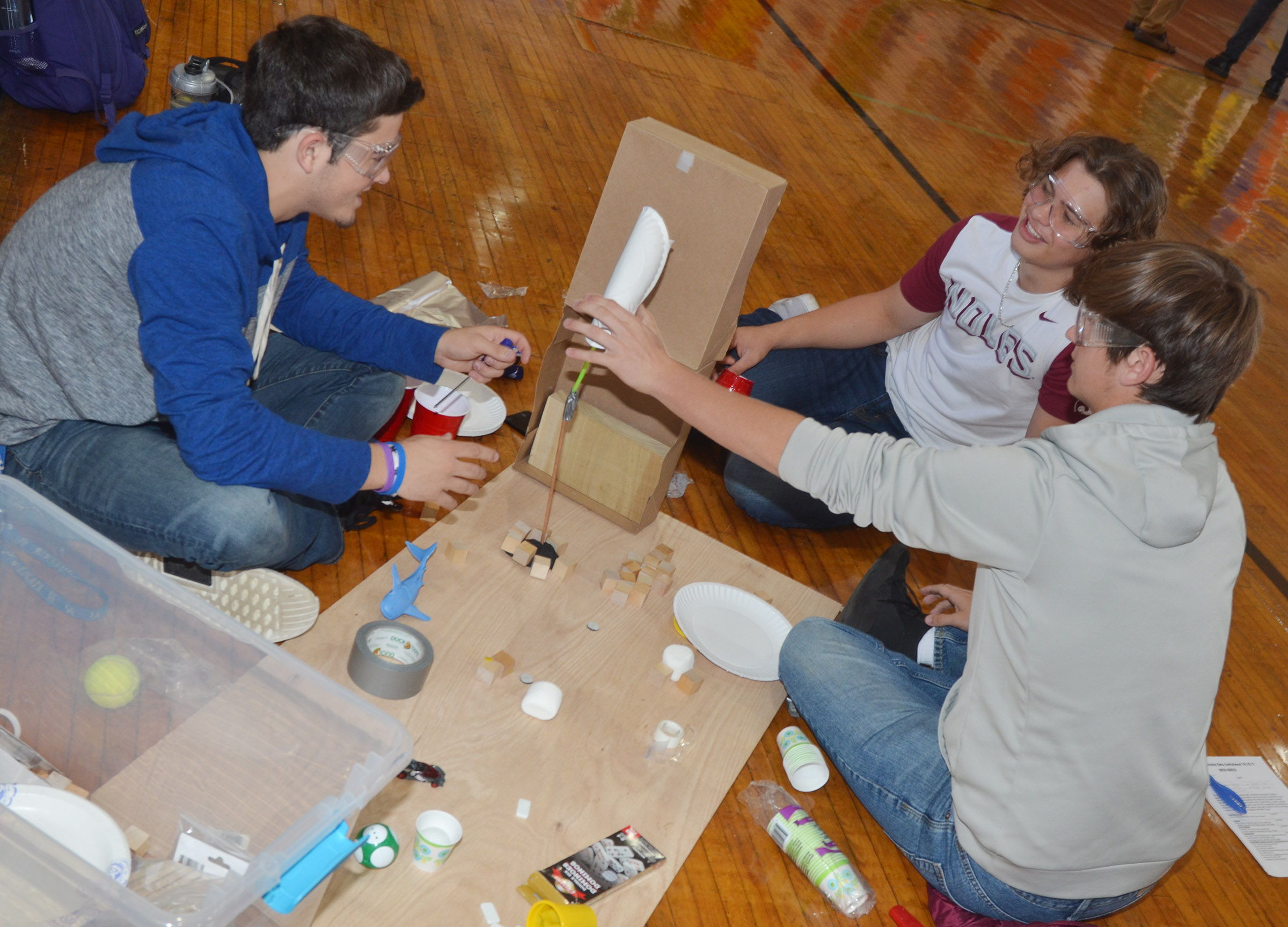 From left, CHS juniors Ryan Kearney, Treyce Mattingly and Myles Murrell build their Rube Goldberg machine in the design build competition.