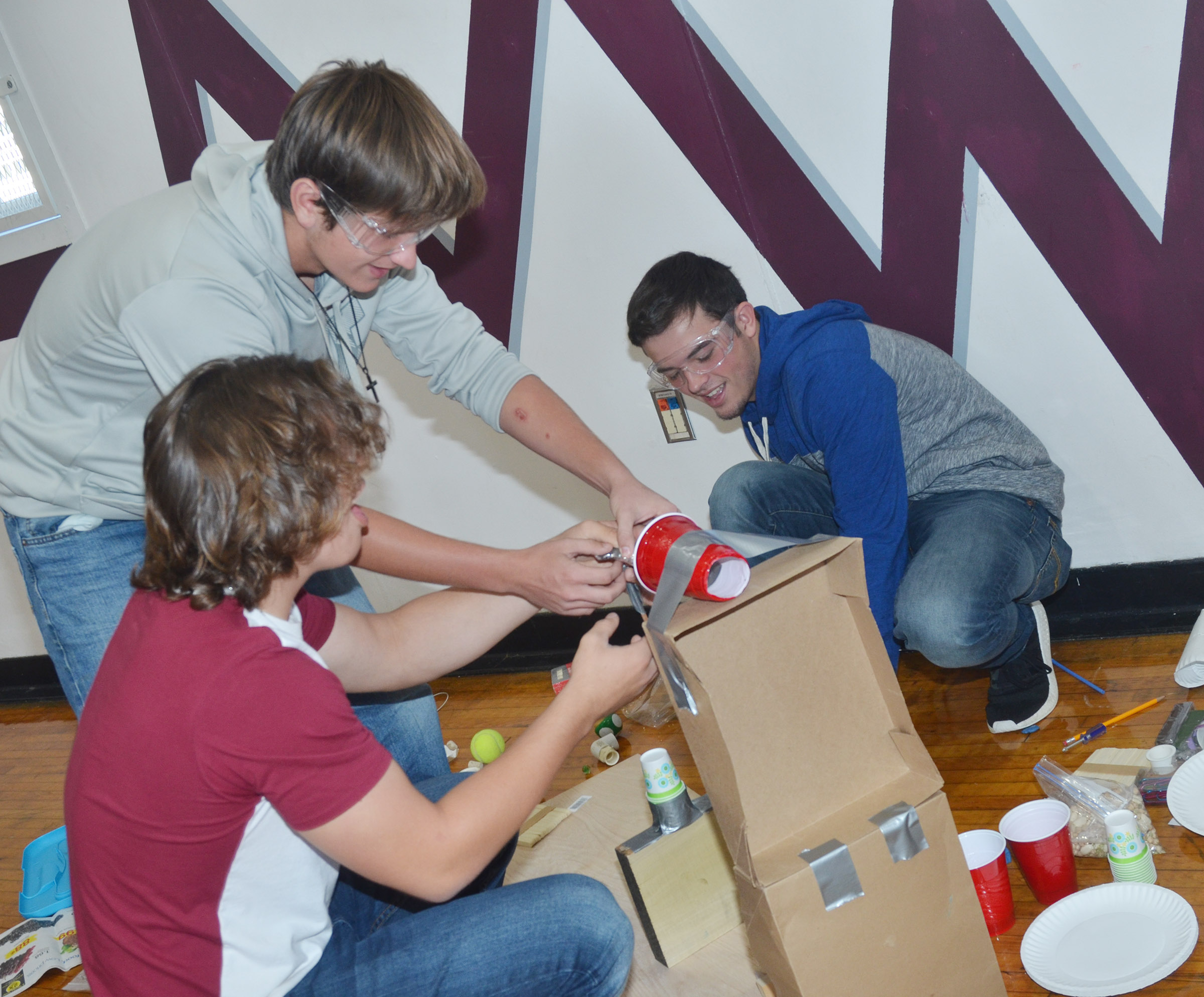 From left, CHS juniors Treyce Mattingly, Myles Murrell and Ryan Kearney build their Rube Goldberg machine in the design build competition.