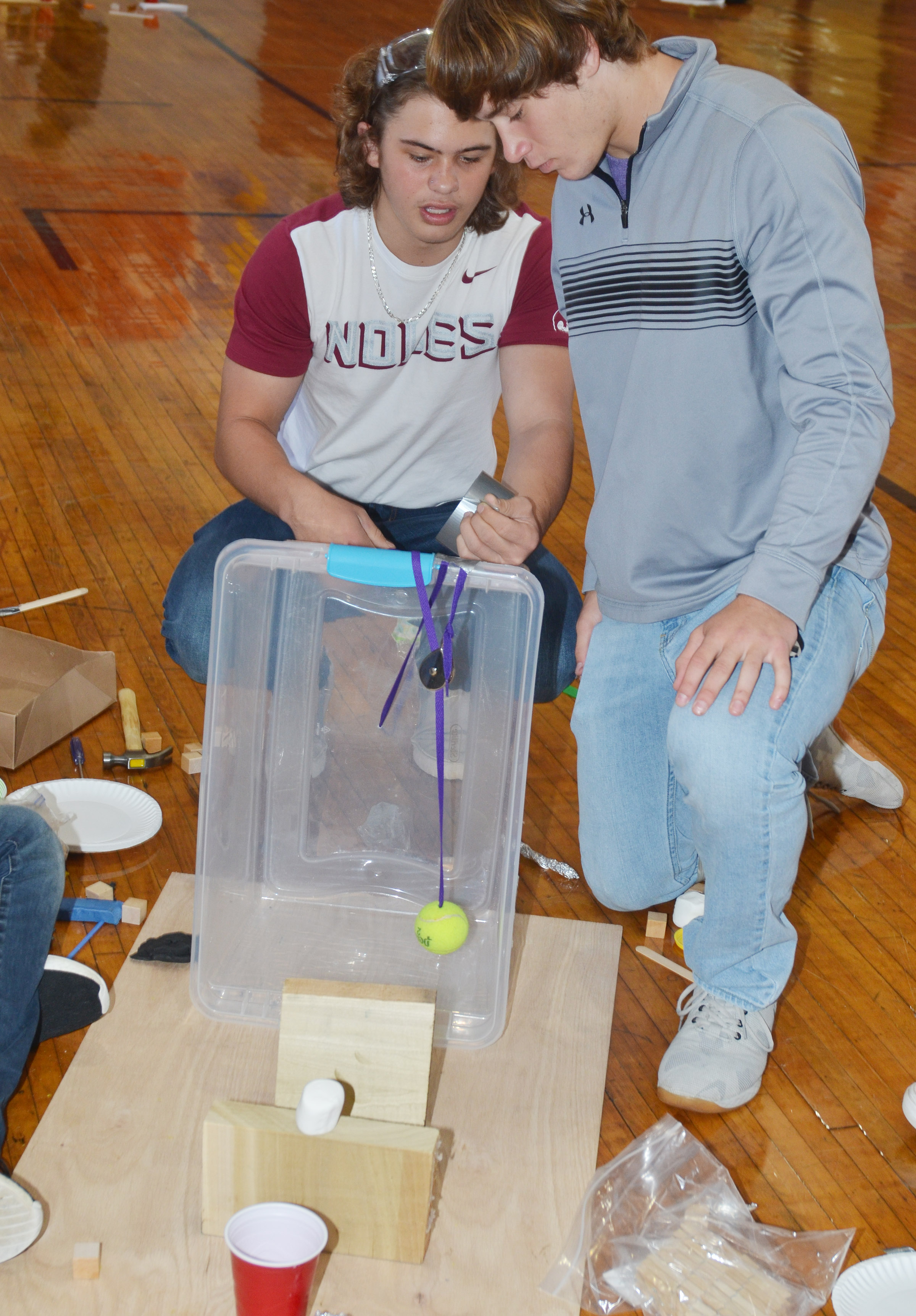 CHS juniors Treyce Mattingly, at left, and Tristan Johnson build their Rube Goldberg machine in the design build competition.