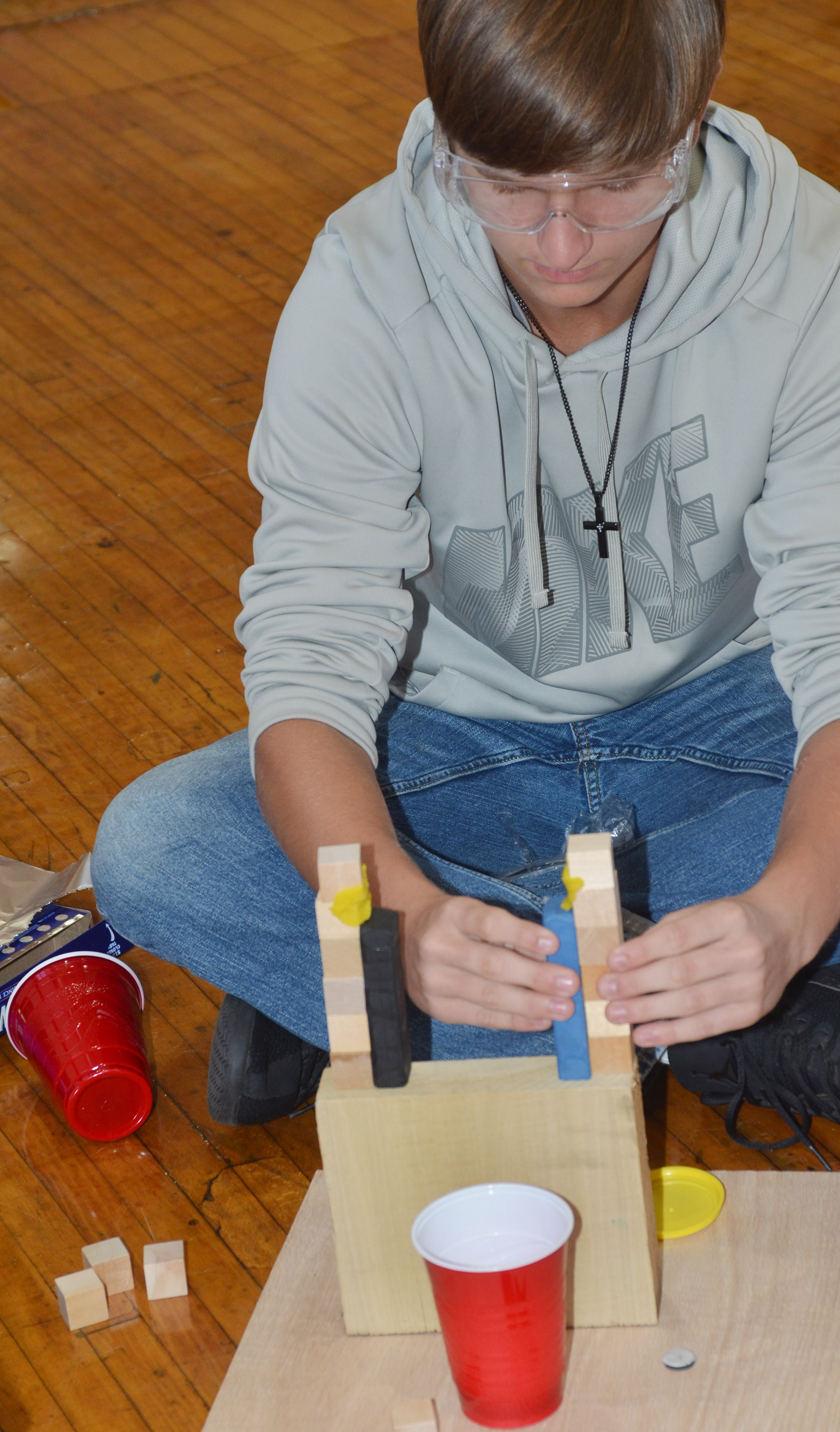 CHS junior Myles Murrell builds his group's Rube Goldberg machine in the design build competition.