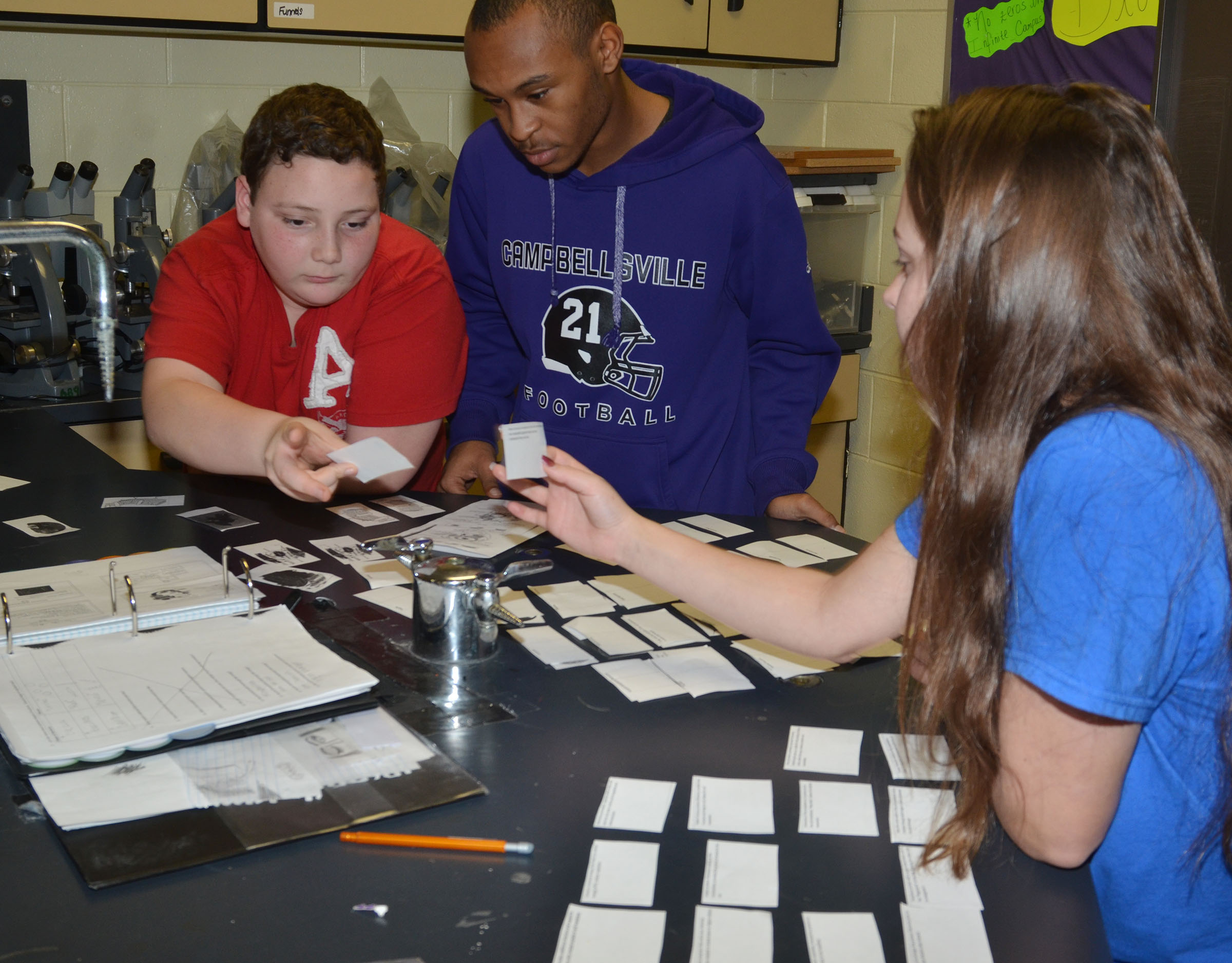 From left, CHS freshman Braydon Phillips and sophomores Daesean Vancleave and Christa Riggs match their photos of the parts of a cell to their names.