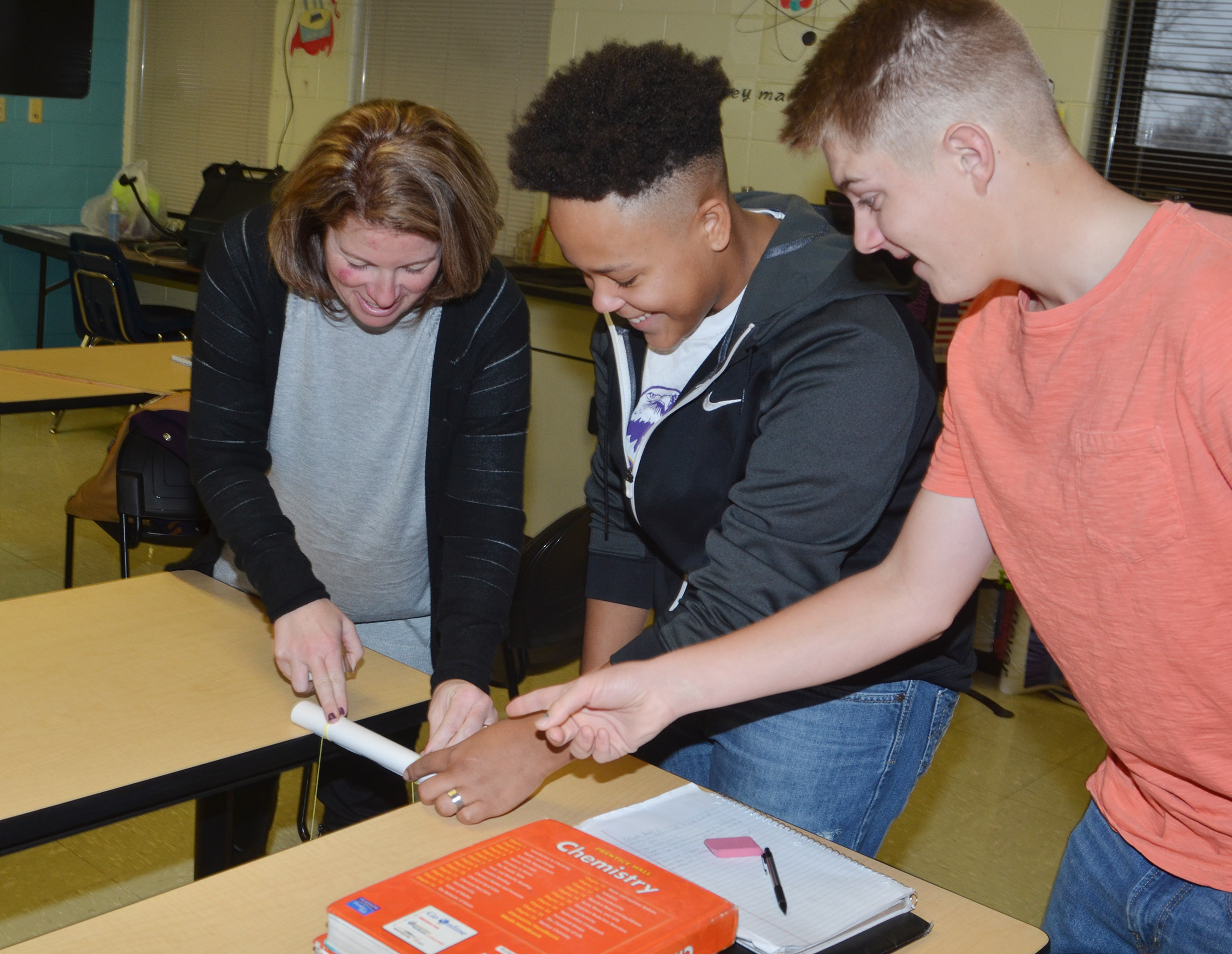 "CHS teacher Dee Doss, at left, helps students Dee Simpson, a sophomore, and junior Alex Doss tie a bag to their ""bone"" to see how much force it can withstand."