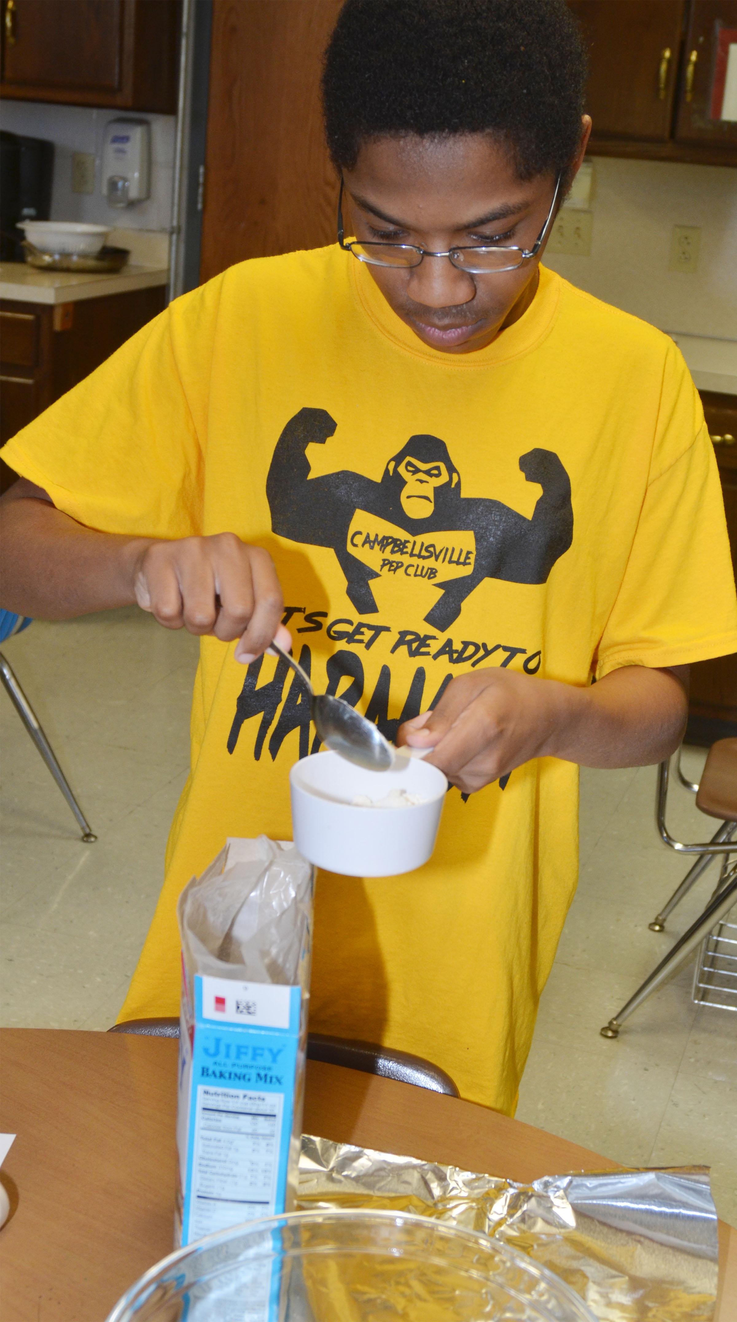 CHS sophomore Travis Nash measures baking mix to make cheesy garlic biscuits.