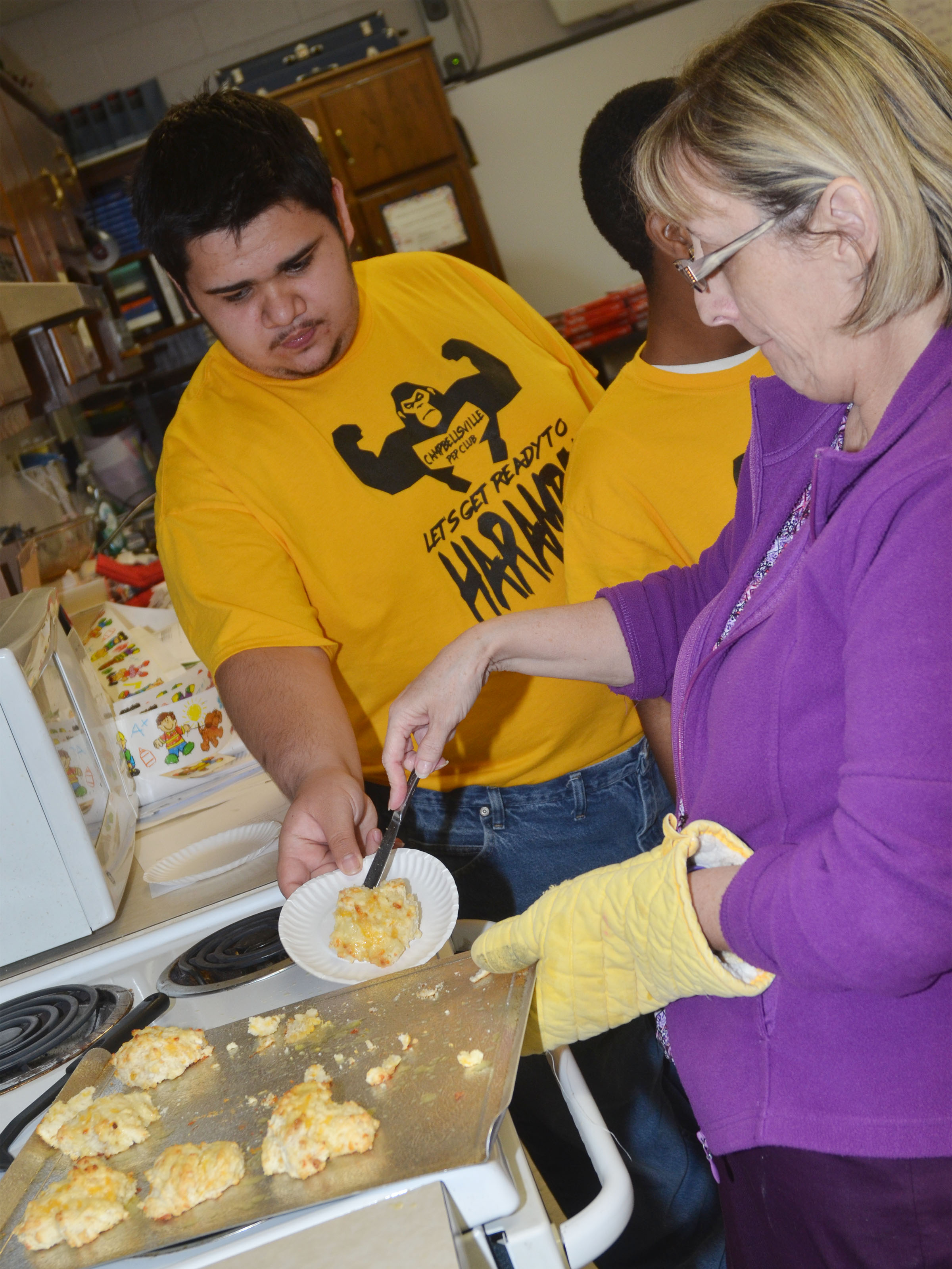 CHS special education teacher Juanita Young serves senior Robert Tungate a cheesy garlic biscuit.