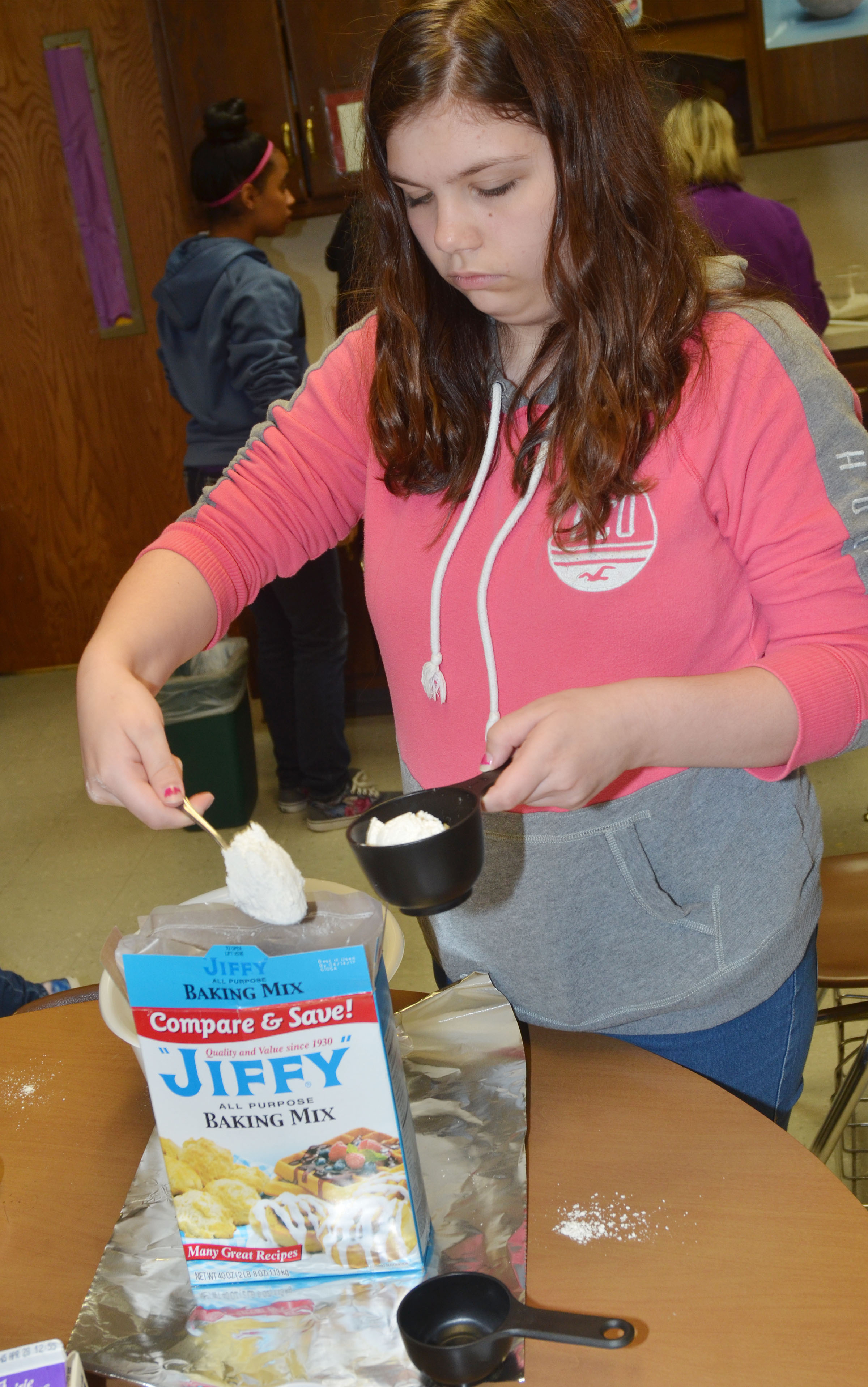 CHS freshman Shelby Hunt measures baking mix to make cheesy garlic biscuits.