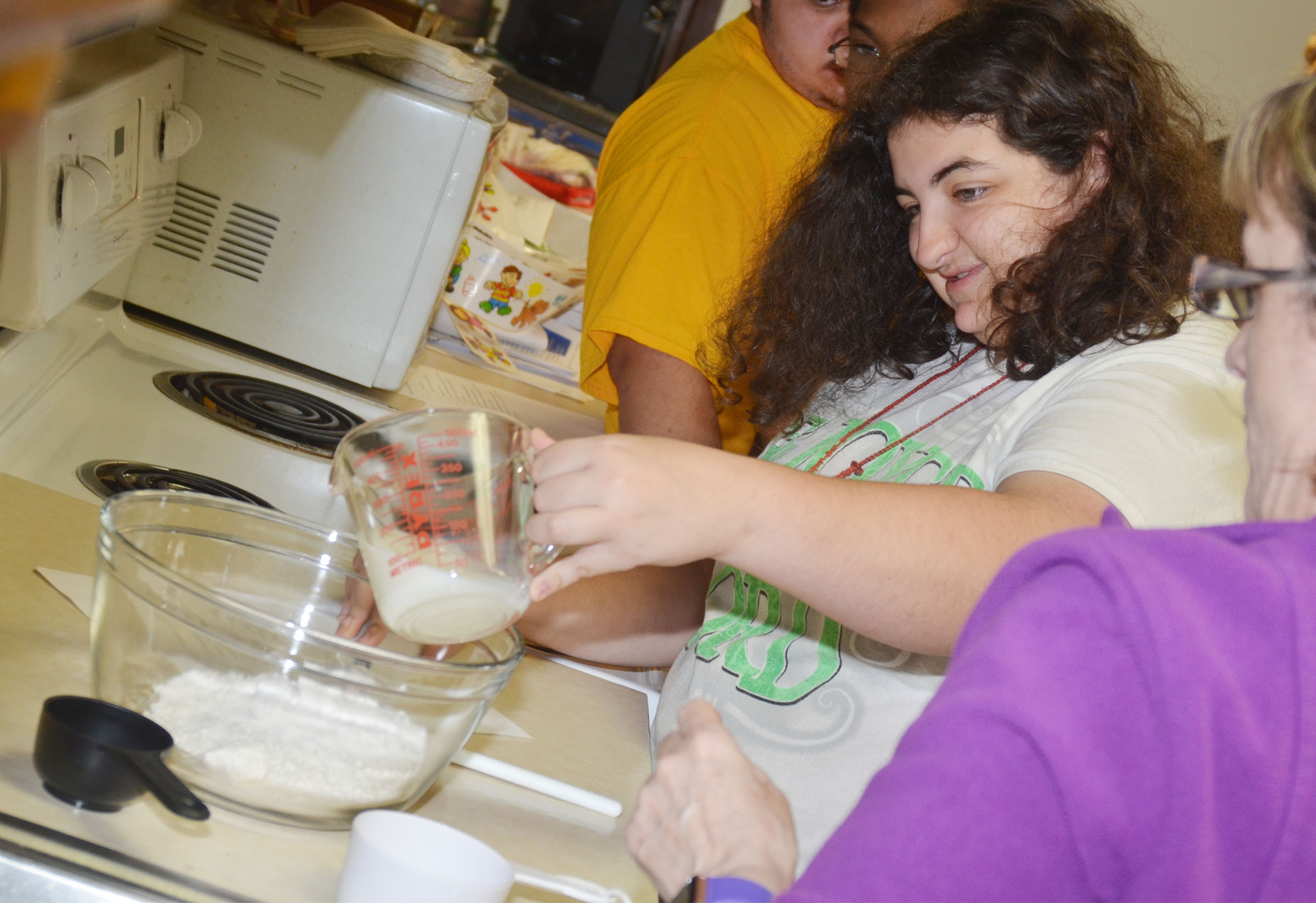 CHS sophomore Brooke Tucker pours milk into the baking mix to make cheesy garlic biscuits.