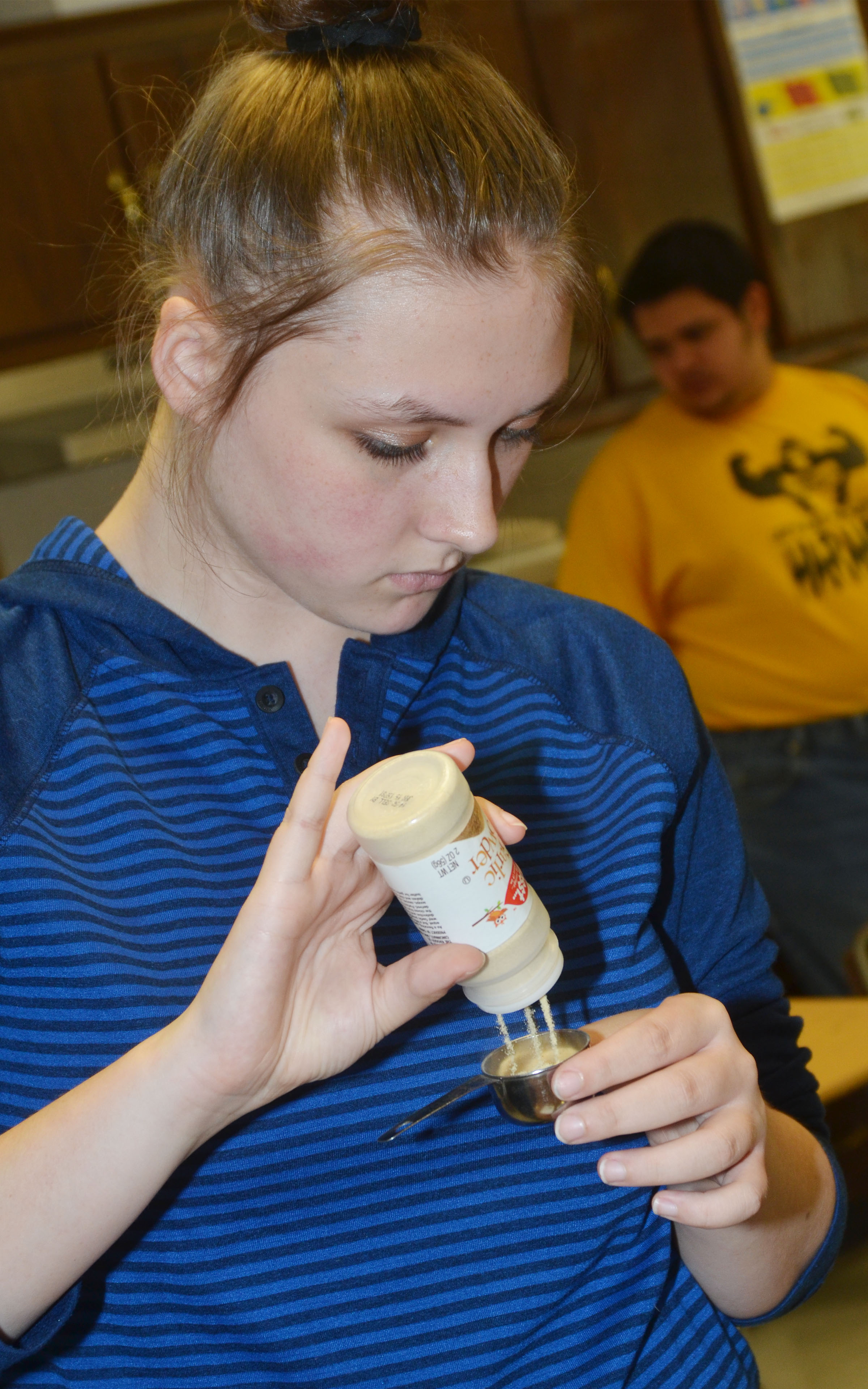 CHS freshman Theresa Underwood measures garlic to make cheesy garlic biscuits.