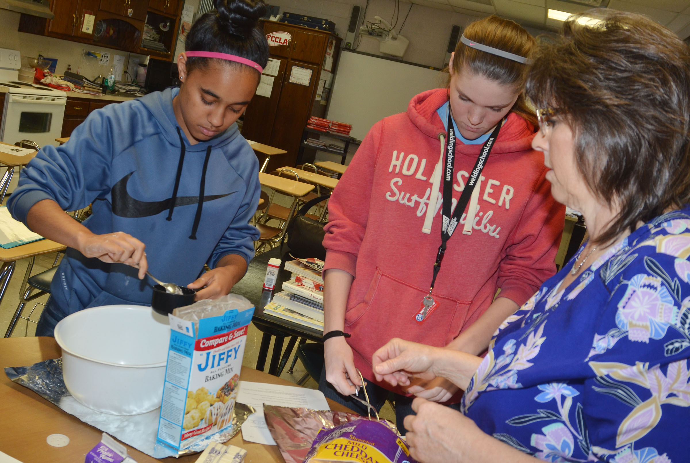 CHS freshman Jasmine Coro, at left, and sophomore Cassi Pipes measure ingredients for their cheesy garlic biscuits, with help from teacher Deanna Campbell.