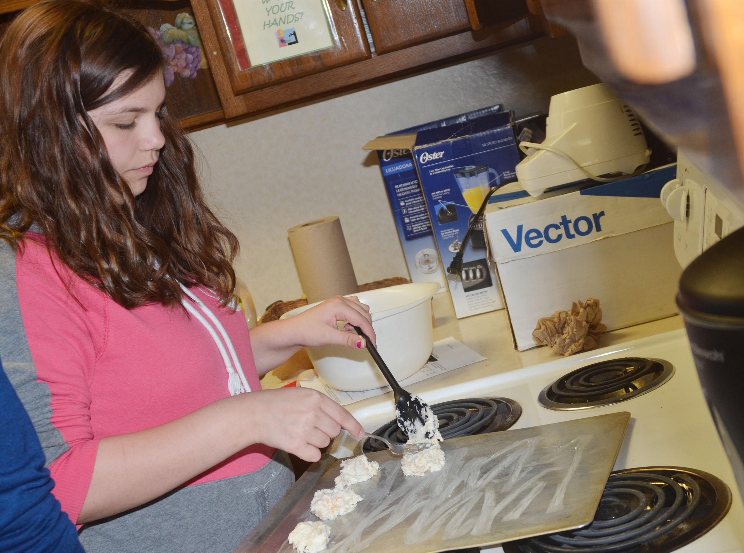 CHS freshman Shelby Hunt places her cheesy garlic biscuits on a baking sheet.