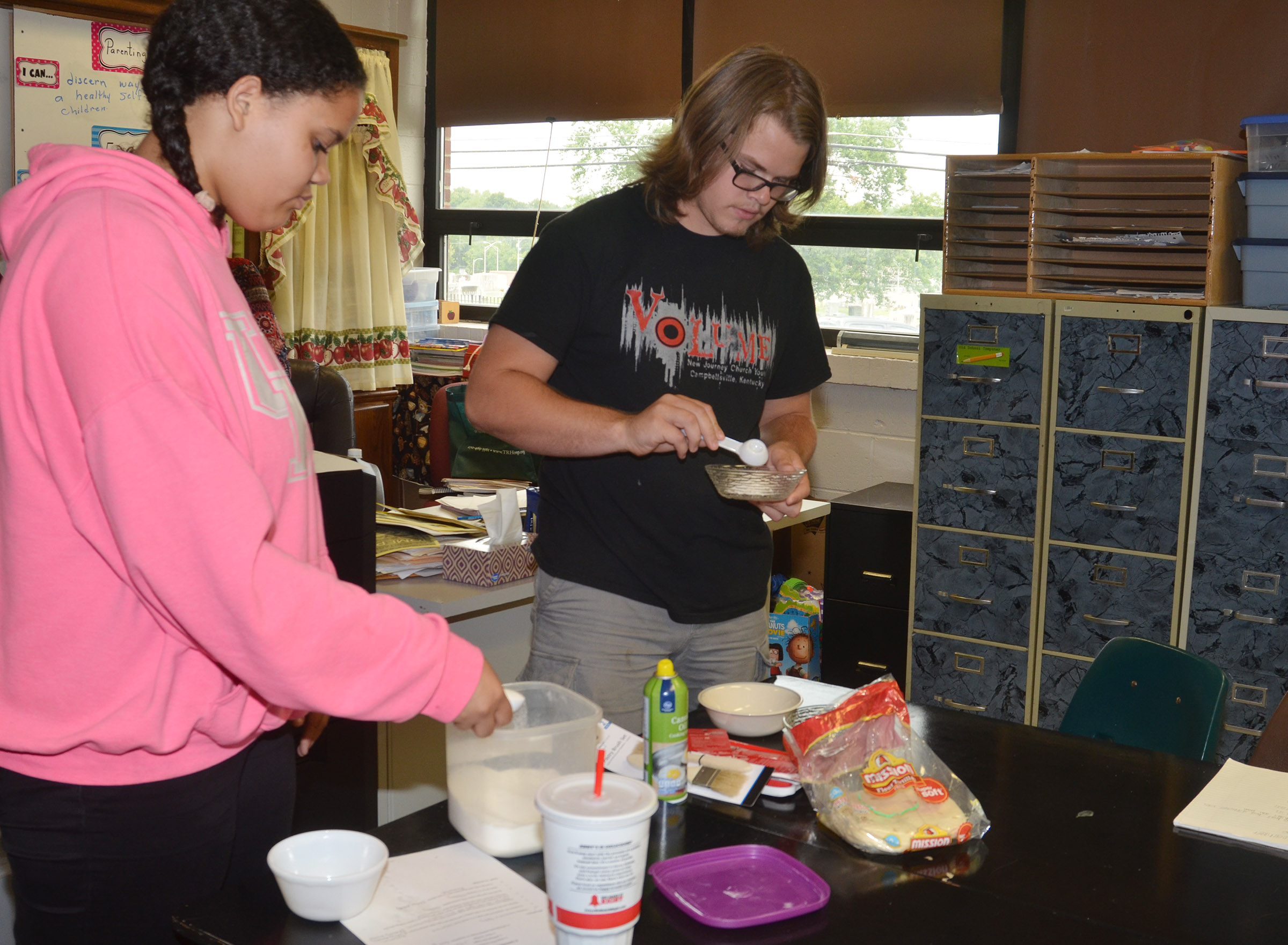 CHS freshman Jasmine Francis, at left, and junior John Netherland measure their ingredients.