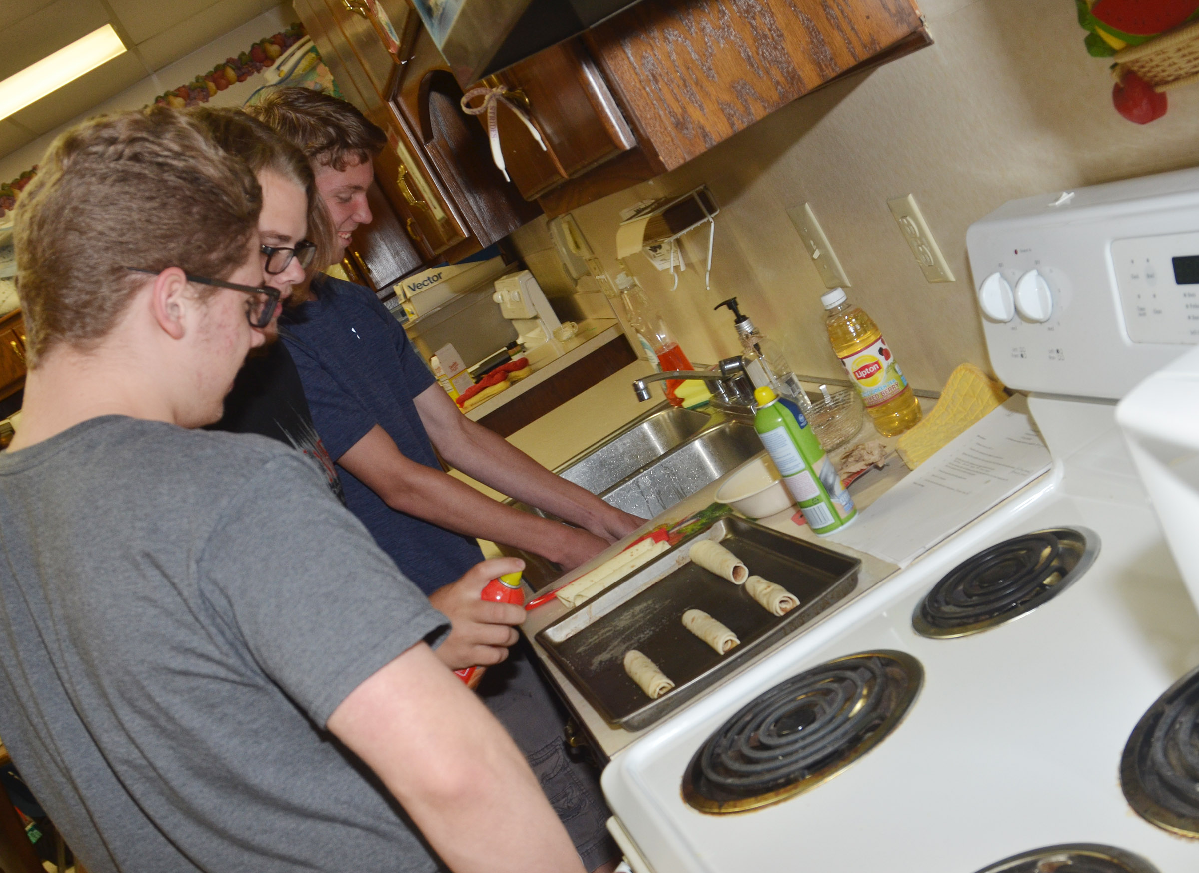 From left, CHS senior Nicholas Lefever and juniors John Netherland and Payton Reynolds get ready to bake their cinnamon roll-ups.