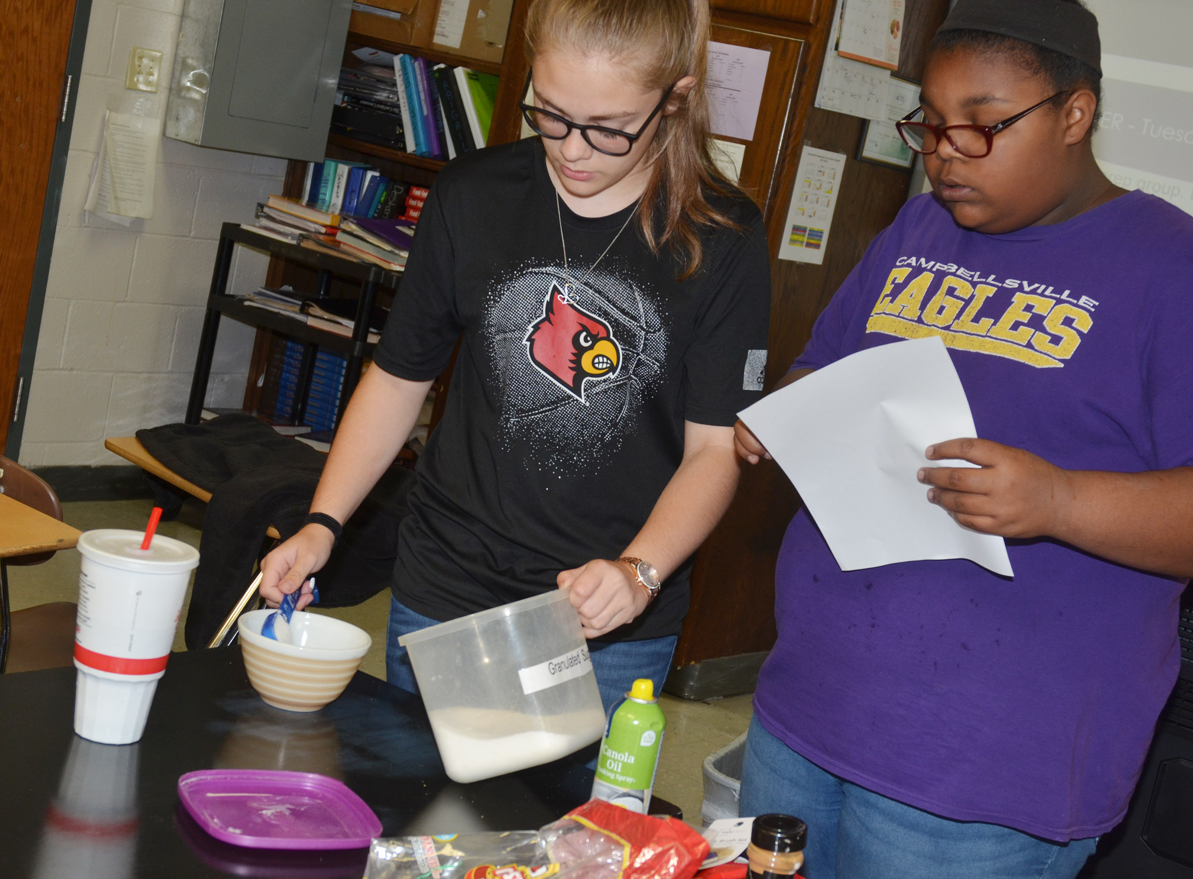 CHS freshmen Emily Kerns, at left, and Destany Lane measure their ingredients.