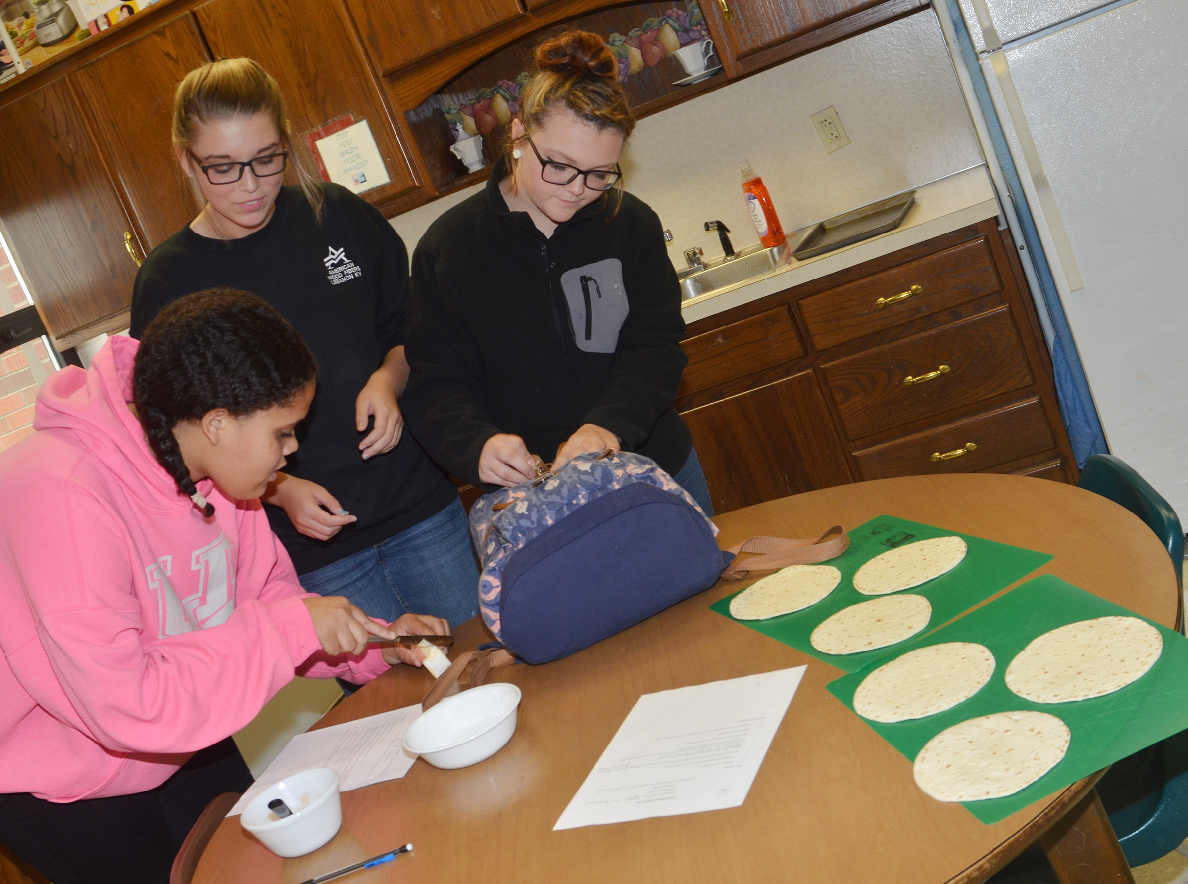 From left, CHS freshmen Jasmine Francis, Autumn Harvey and Abigail Decker melt their butter.