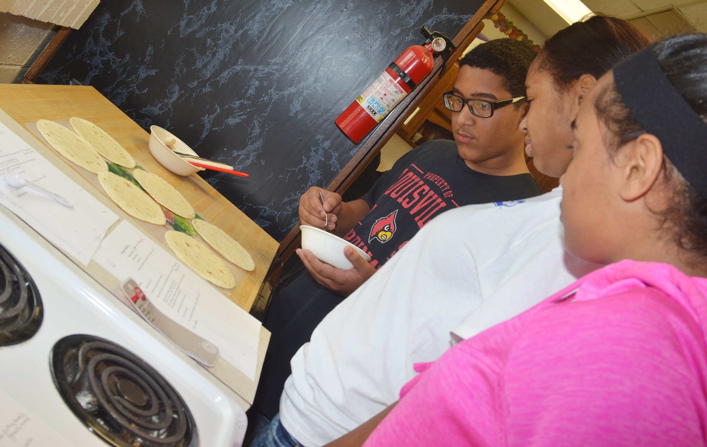 From left, CHS freshman Tyreece Washington and sophomores Isis Coleman and Jasmine Coro follow their recipe.