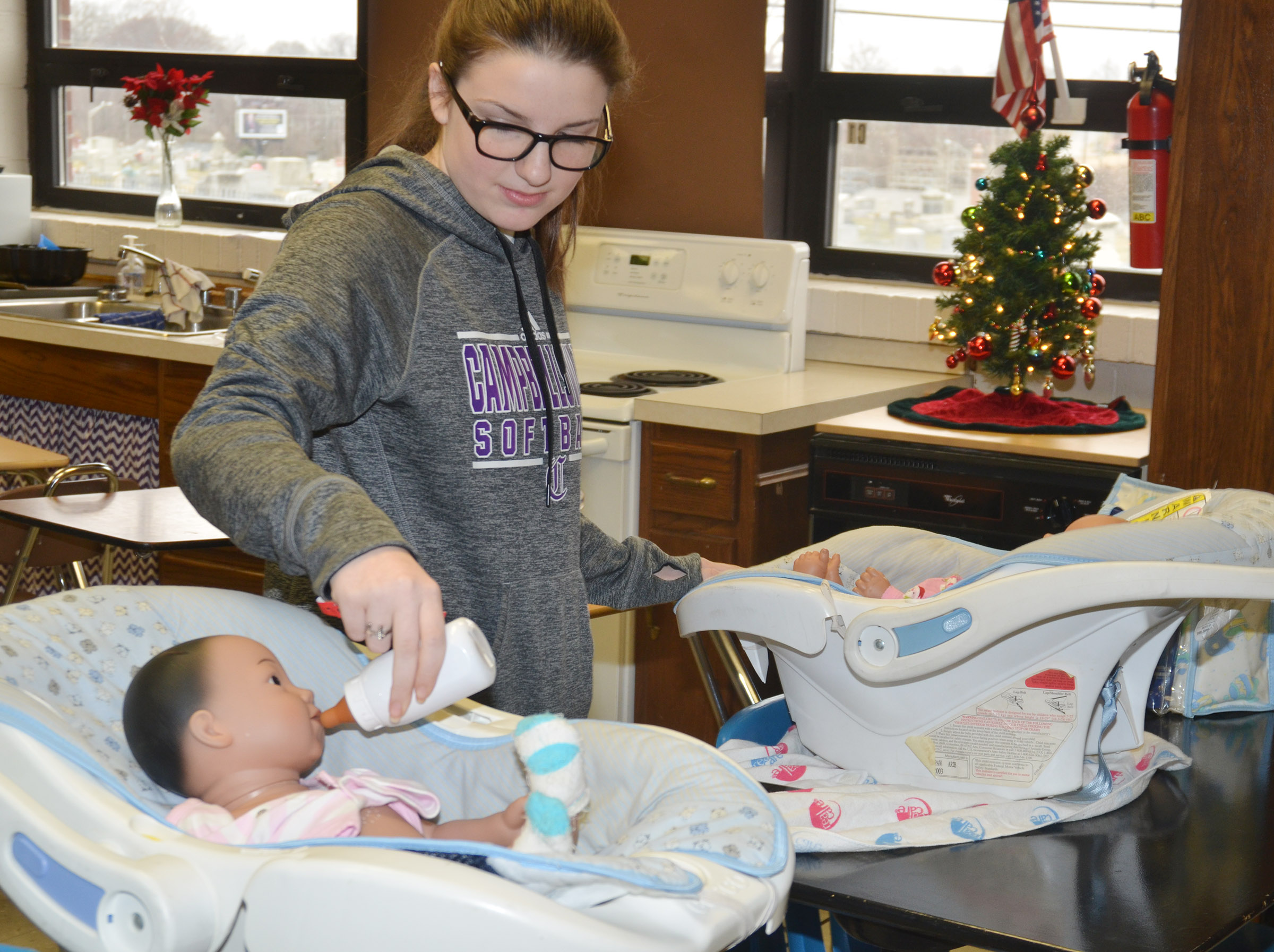 CHS freshman Sydney Wilson feeds one baby while rocking another.