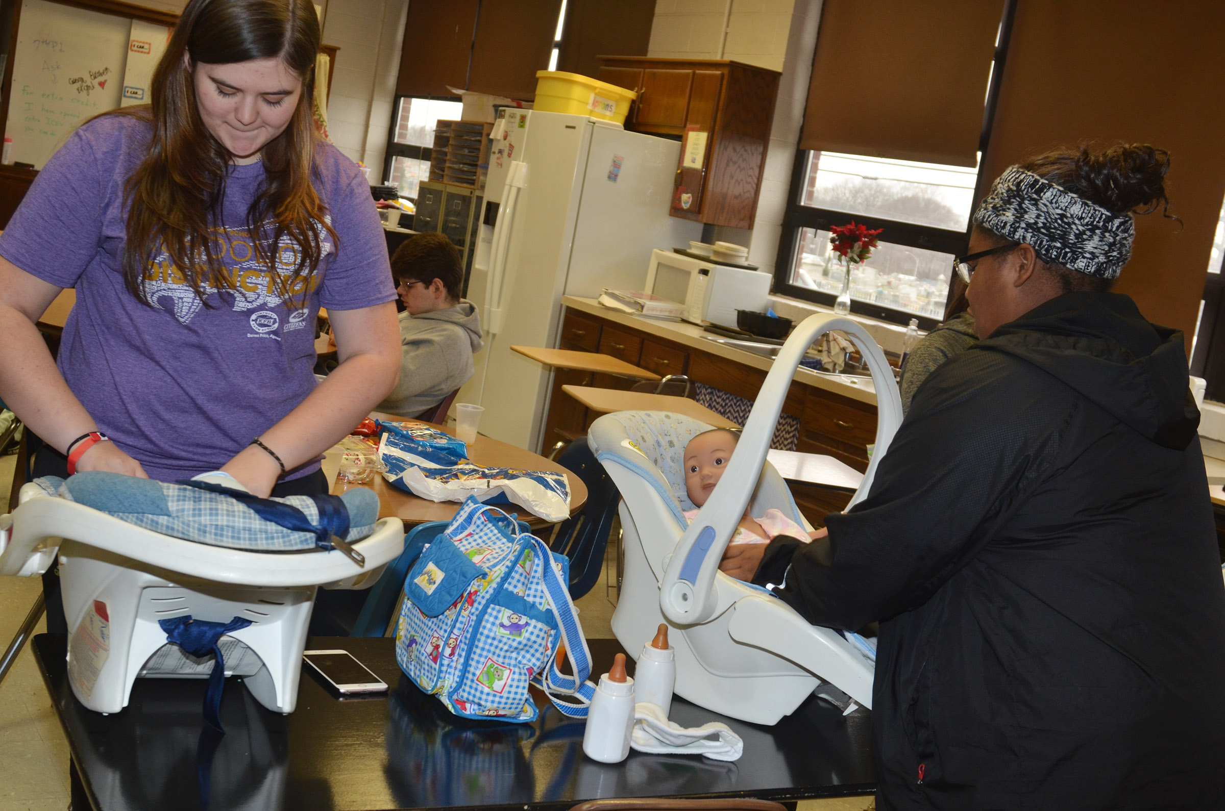 CHS junior Vivian Brown, at left, and freshman Jakyia Mitchell place their babies in car seats.