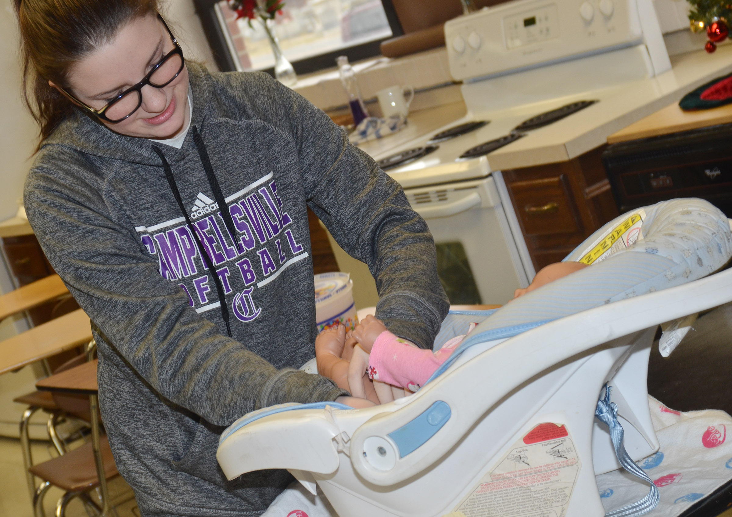 CHS freshman Sydney Wilson places her baby in a child seat.