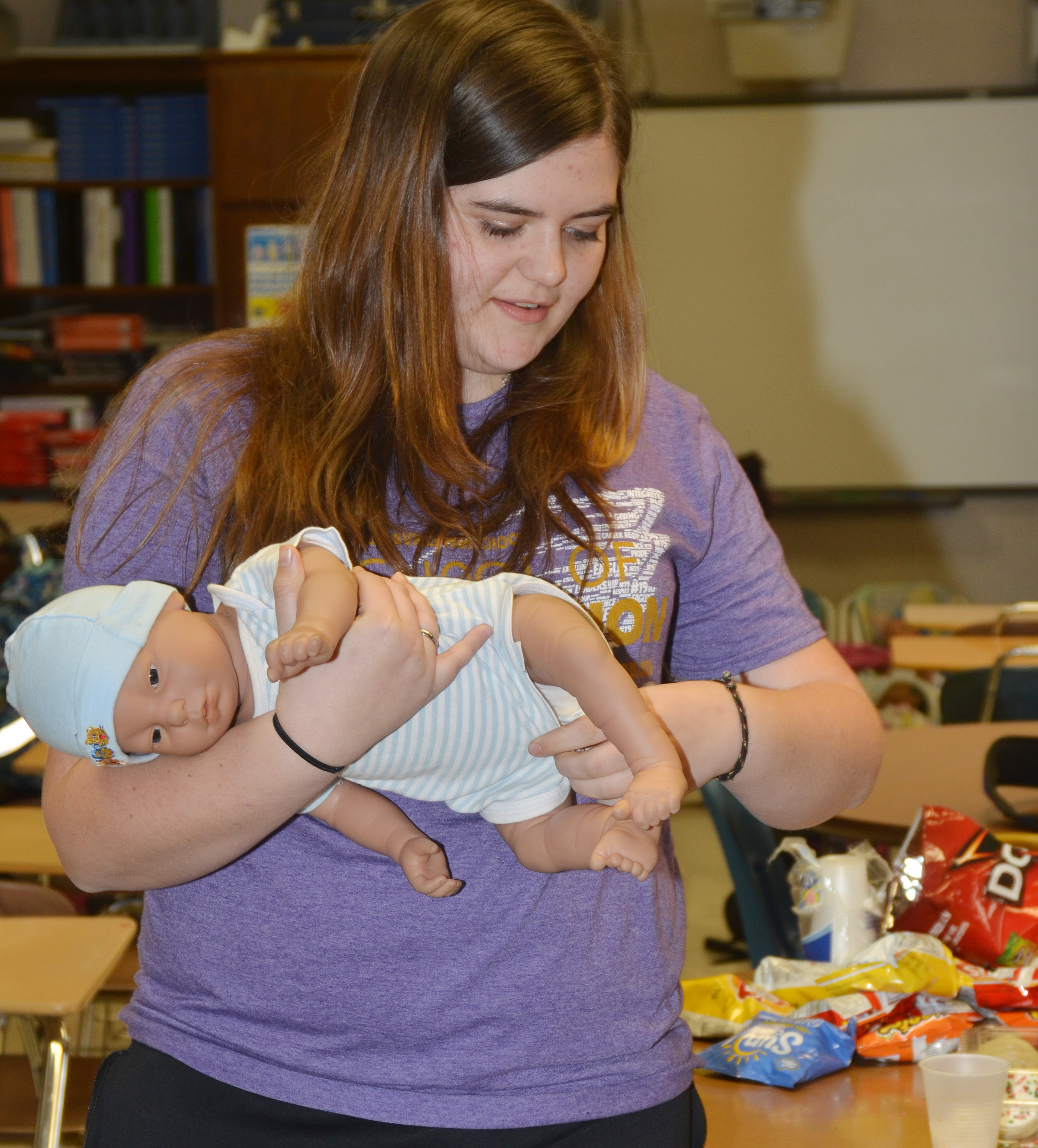 CHS junior Vivian Brown dresses her baby.