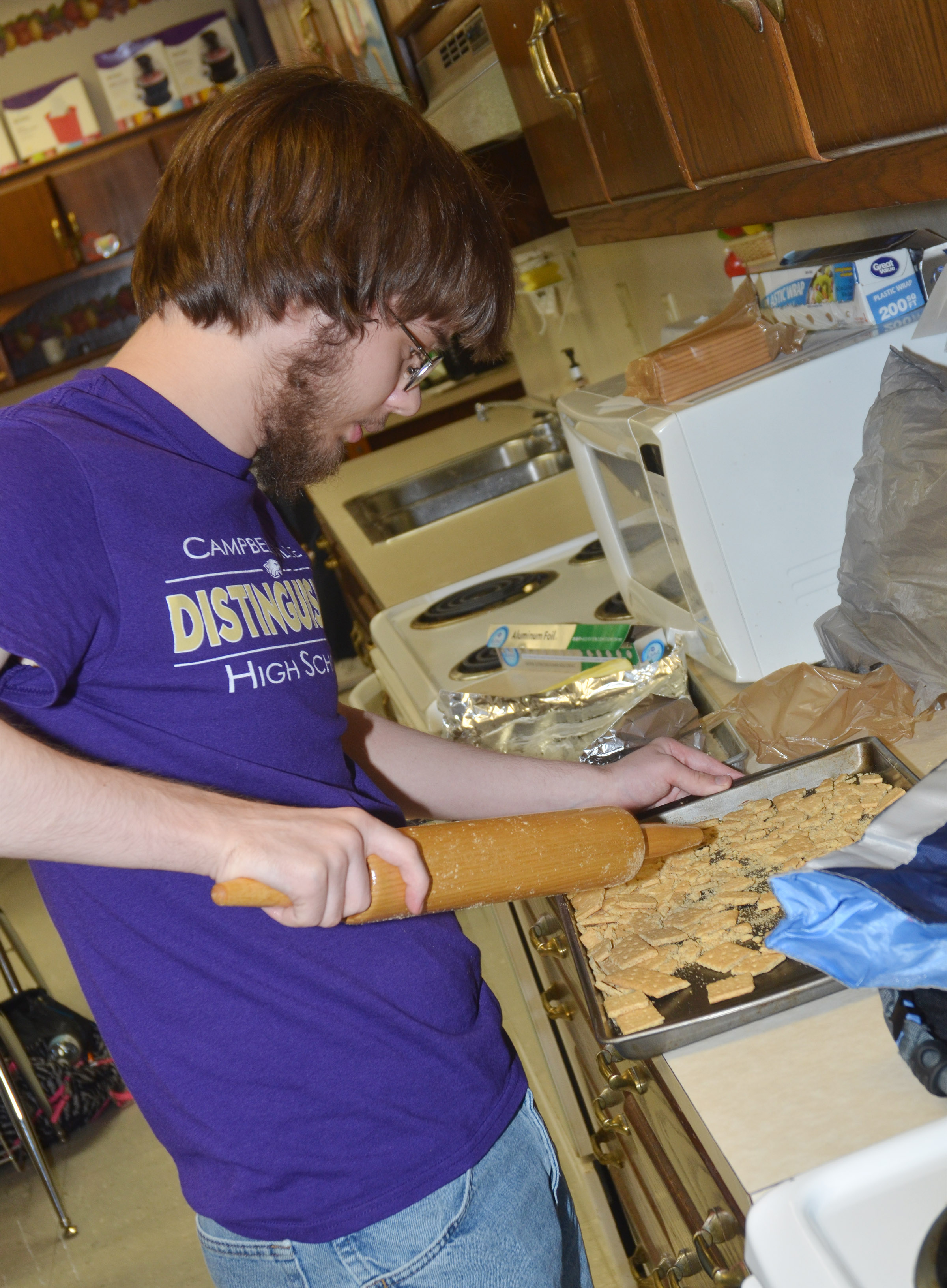 CHS senior Gabriel Clark crushes graham crackers as he makes his dessert for his final project.
