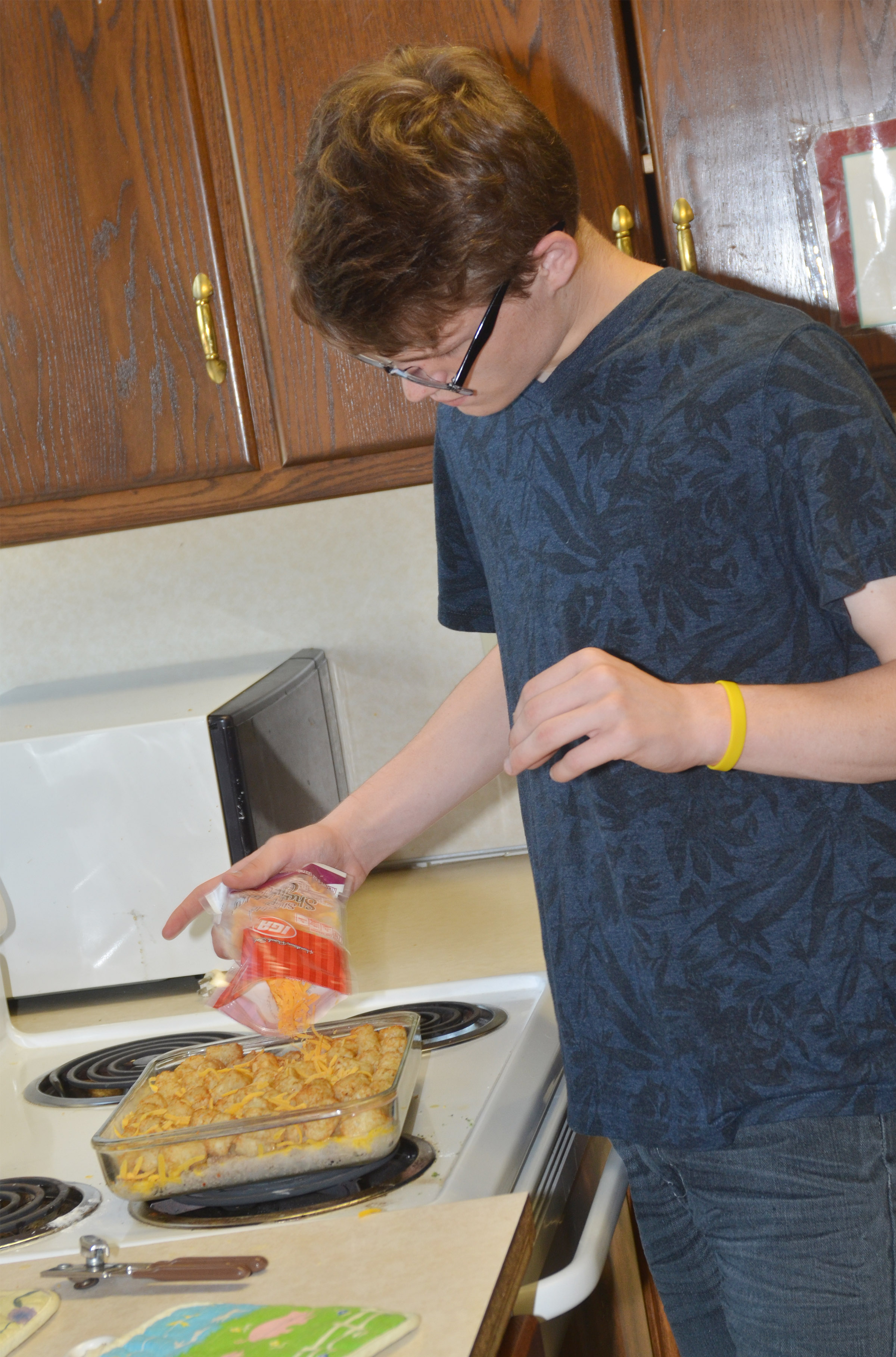 CHS sophomore Joe Pipes adds cheese to the breakfast casserole he made for his final project.