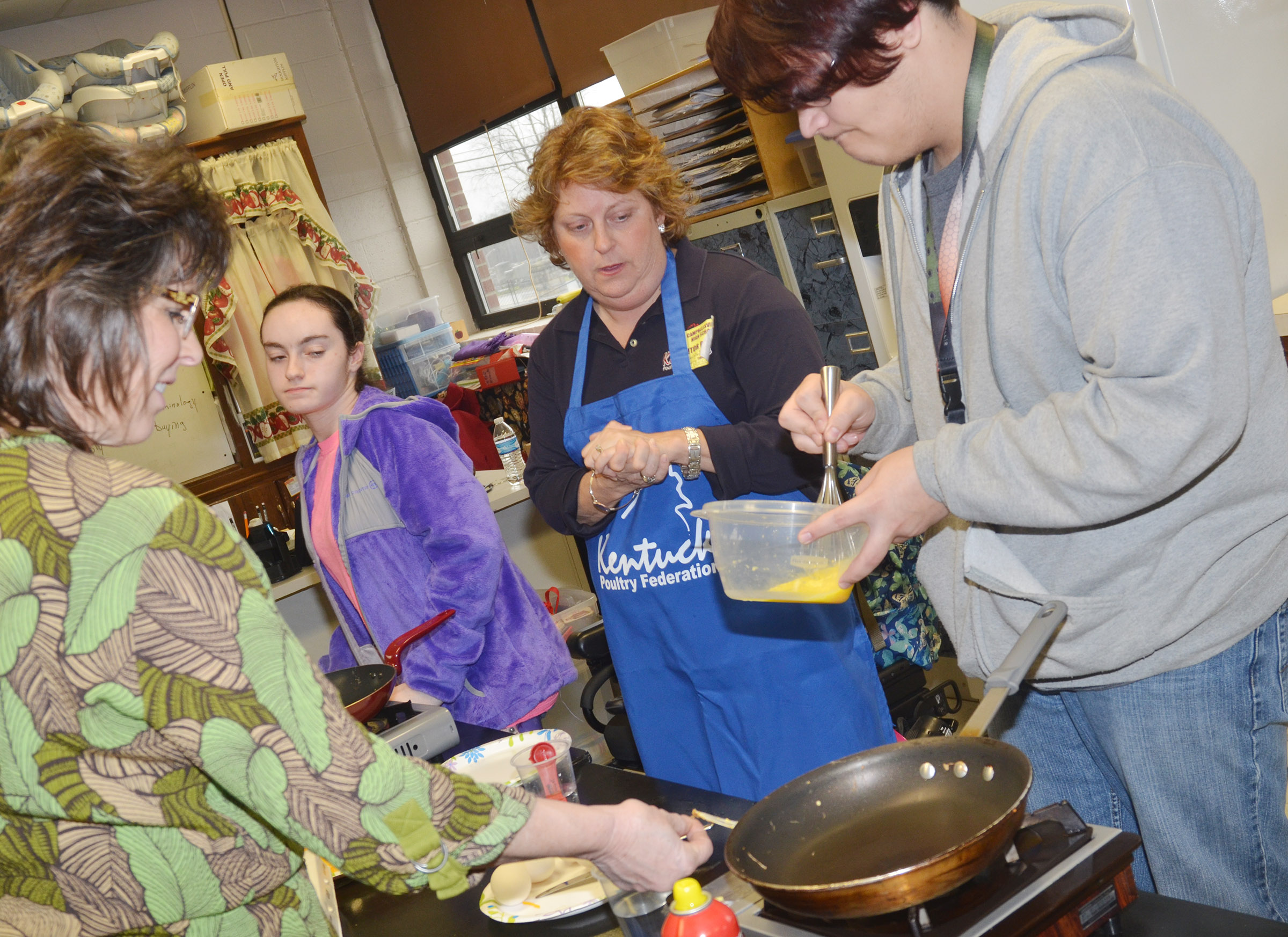 "CHS teacher Deanna Campbell, at left, and Cassinda Bechanan, promotions coordinator with the Kentucky Poultry Federation, known around the state as the ""Egg Lady,"" center, watch as junior Aidan McMahan pours his egg mixture into his pan."