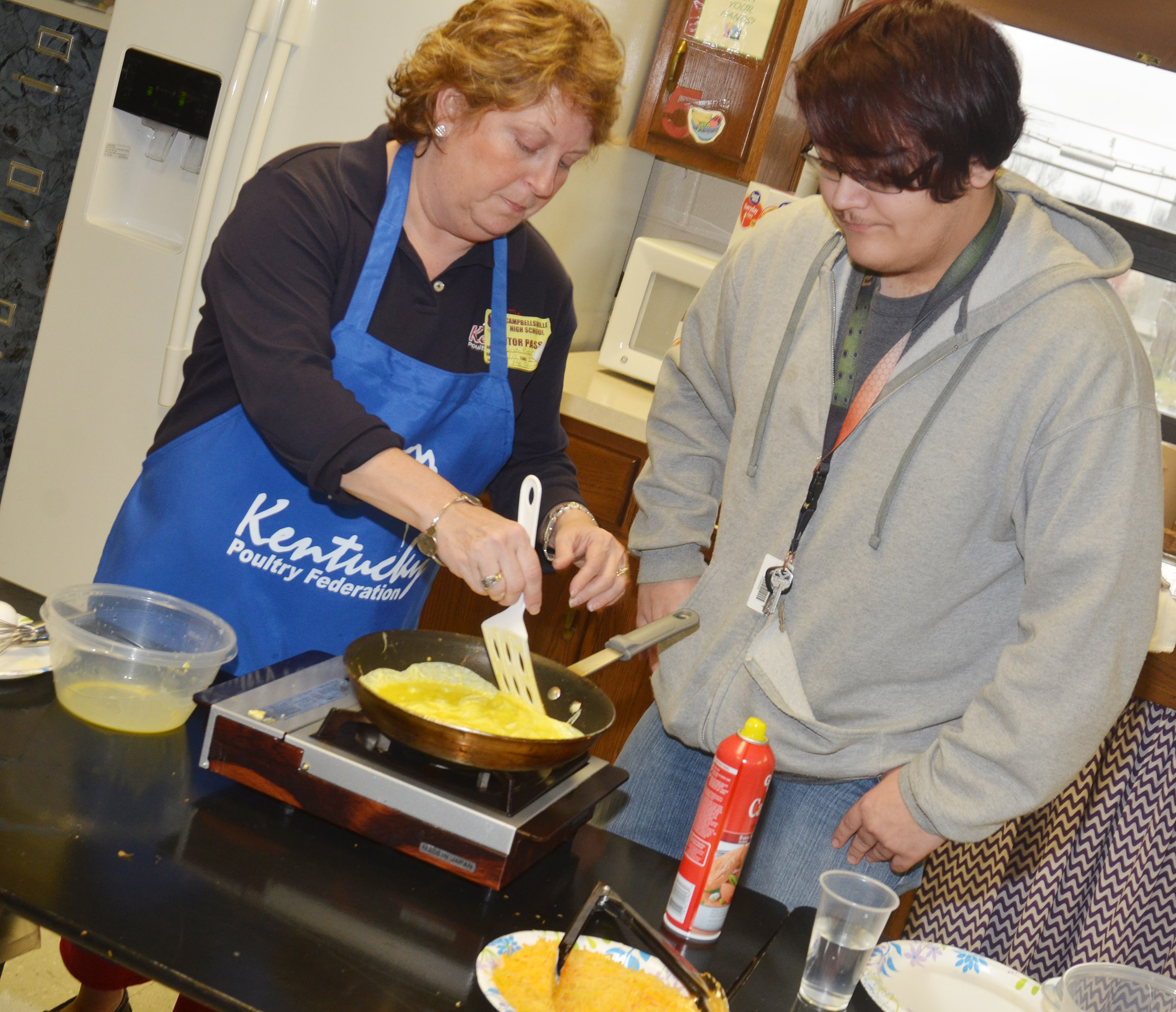 "Cassinda Bechanan, promotions coordinator with the Kentucky Poultry Federation, known around the state as the ""Egg Lady,"" helps CHS junior Aidan McMahan flip his omelet."