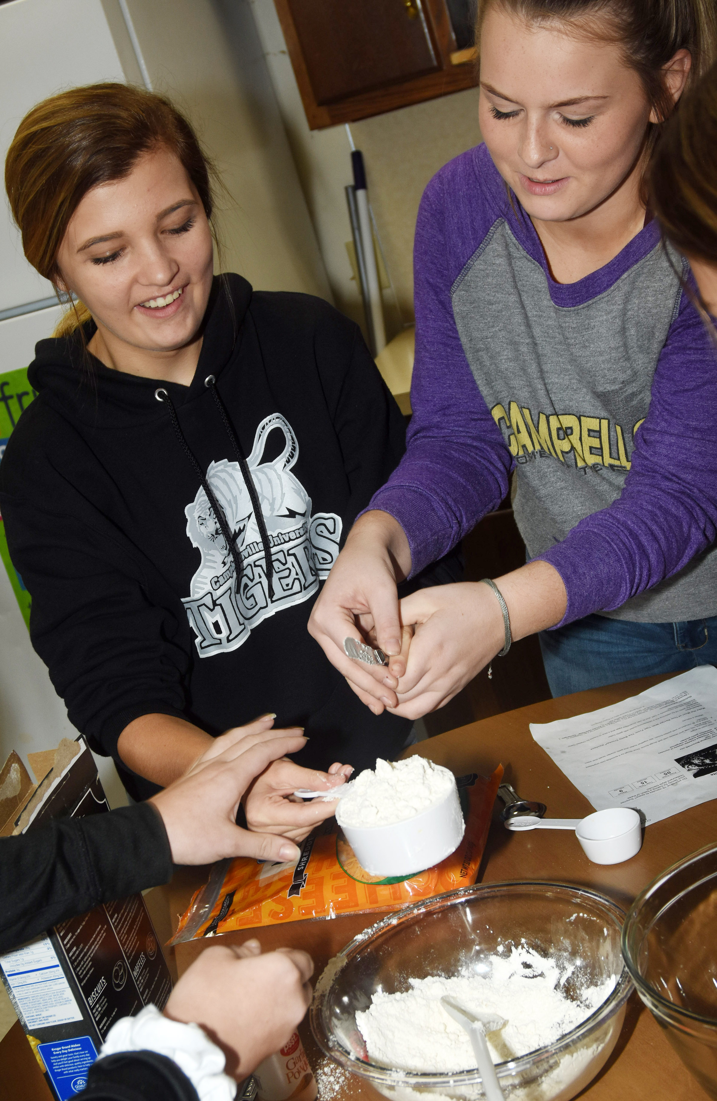 CHS sophomores Carly Adams, at left, and Taylor Knight mix ingredients as they make homemade biscuits.