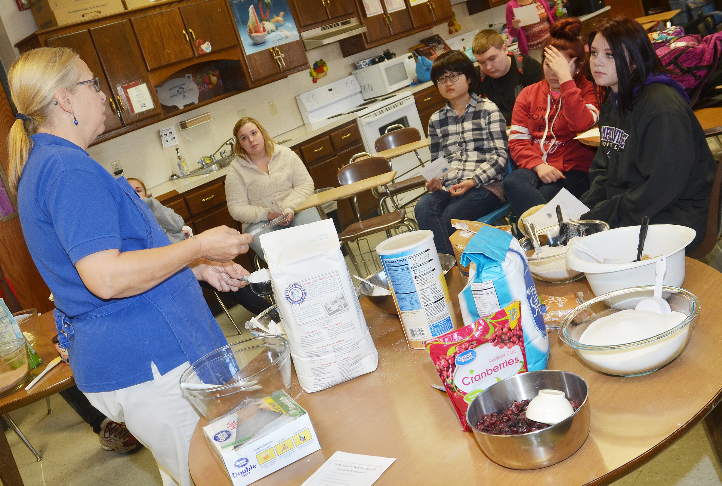 Angie Freeman, expanded foods and nutrition program assistant at Taylor County Extension Office, talks to Deanna Campbell's students about the proper way to measure ingredients.