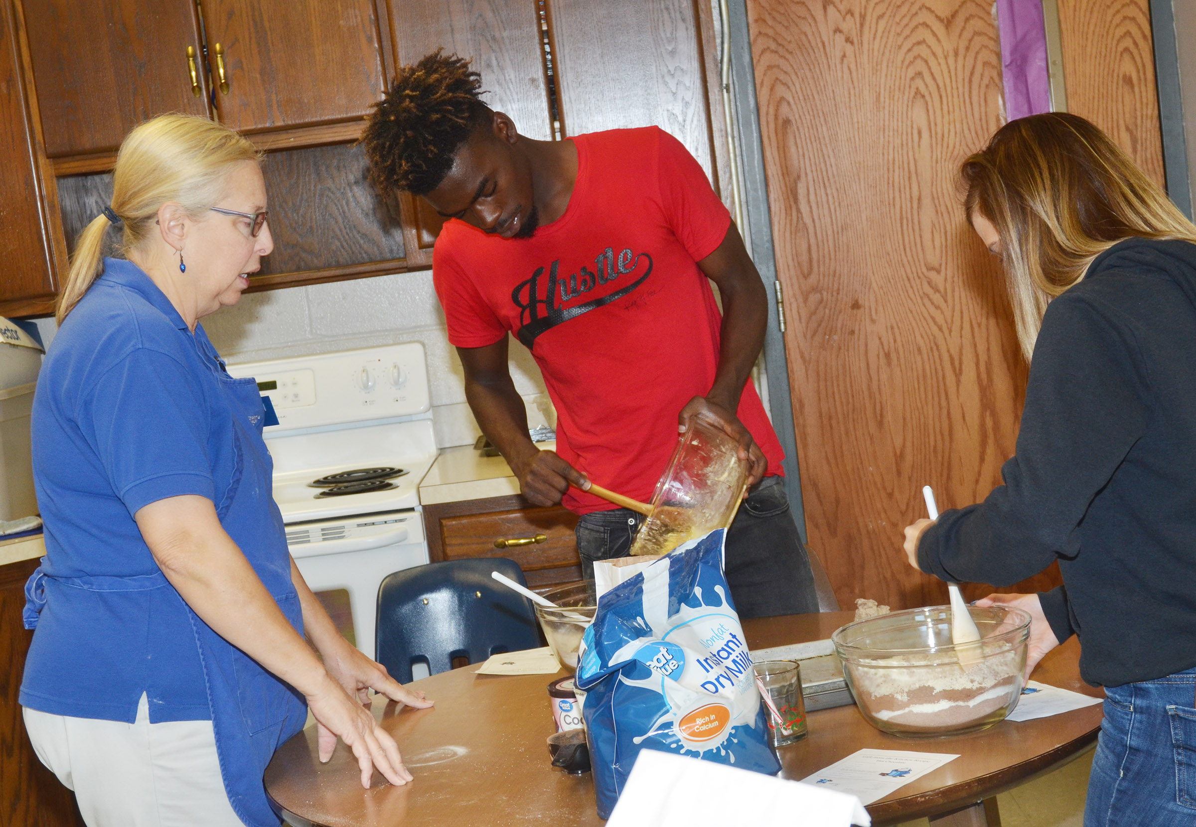 Angie Freeman, expanded foods and nutrition program assistant at Taylor County Extension Office, helps CHS senior Jonta' Strawther and freshman Carly Adams prepare cranberry hootycreeks cookies.