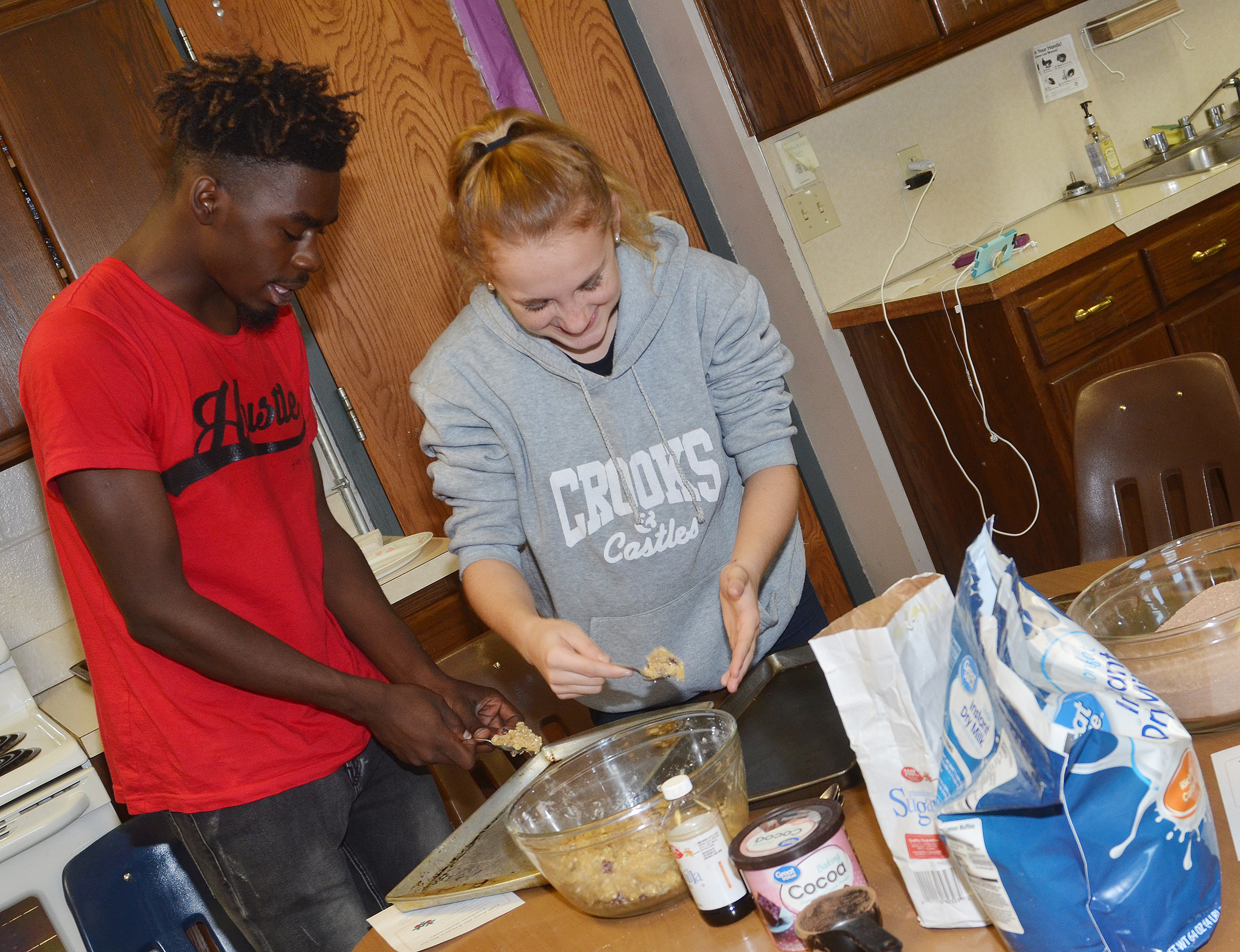 CHS senior Jonta' Strawther, at left, and freshman Gracie O'Rafferty scoop cranberry hootycreeks cookies.