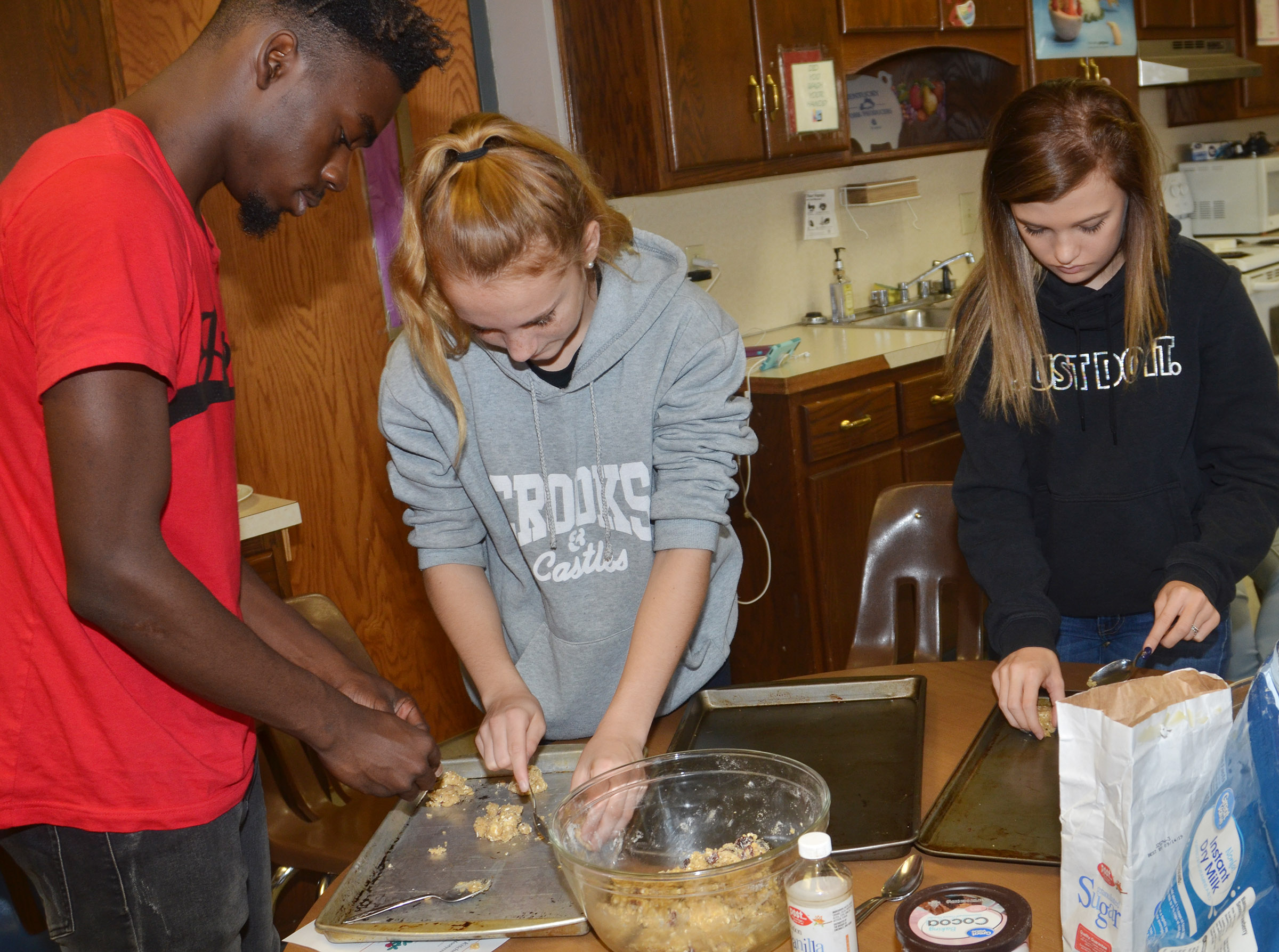 From left, CHS senior Jonta' Strawther and freshmen Gracie O'Rafferty and Carly Adams scoop cranberry hootycreeks cookies.