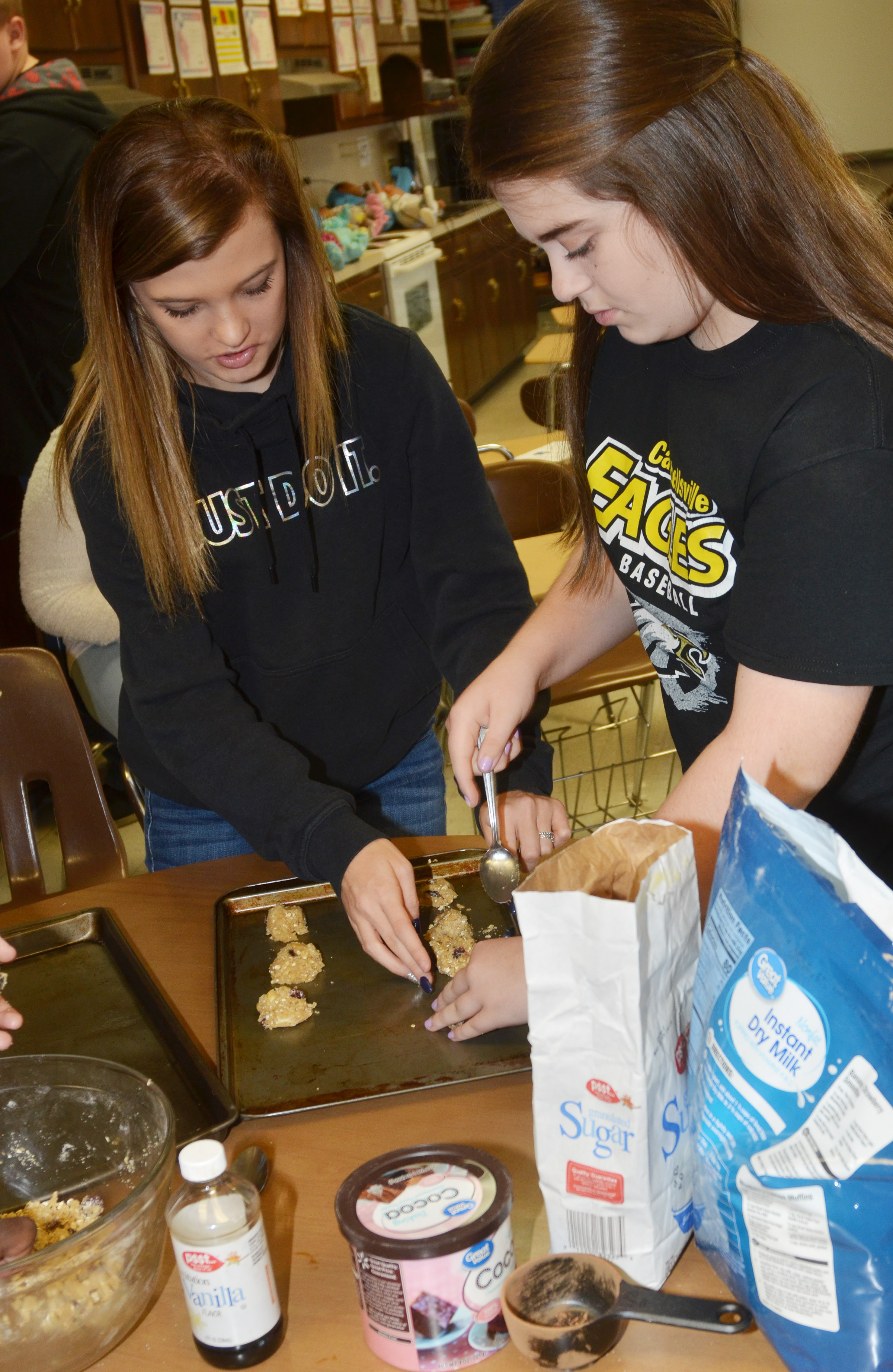 CHS freshmen Carly Adams, at left, and Chloe Garrett scoop cranberry hootycreeks cookies.