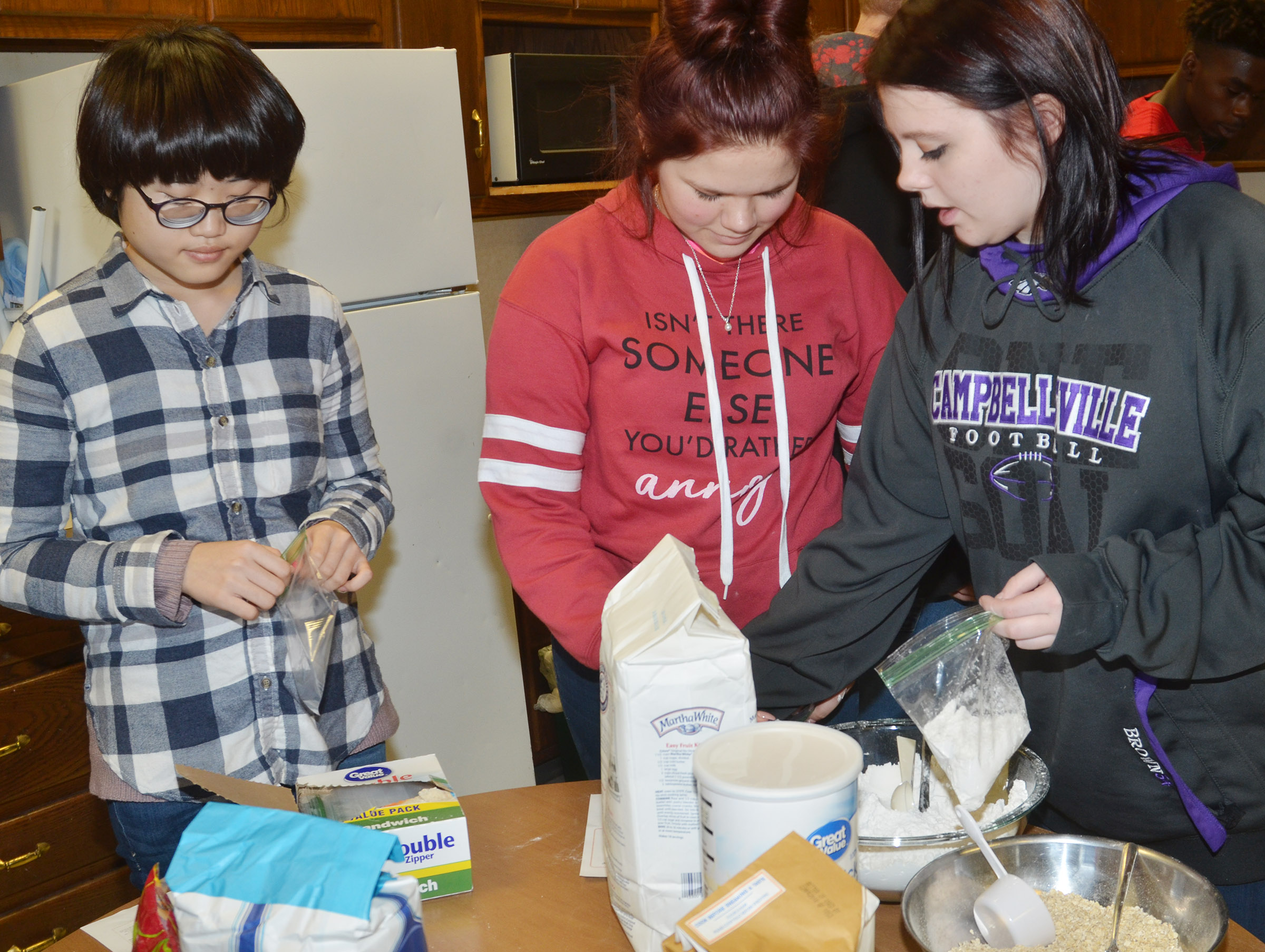 From left, CHS junior Cherry Kim, freshmen Destiny Tungate and senior Kinsey Hampton prepare their cranberry hootycreeks cookie ingredients in a bag.