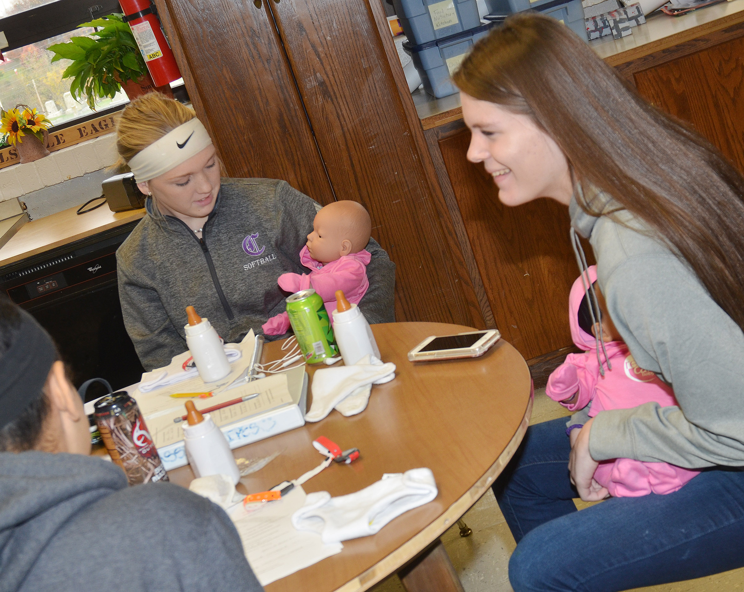 CHS freshman Catlyn Clausen, at left, and junior Cassie Pipes hold their Real Care babies.
