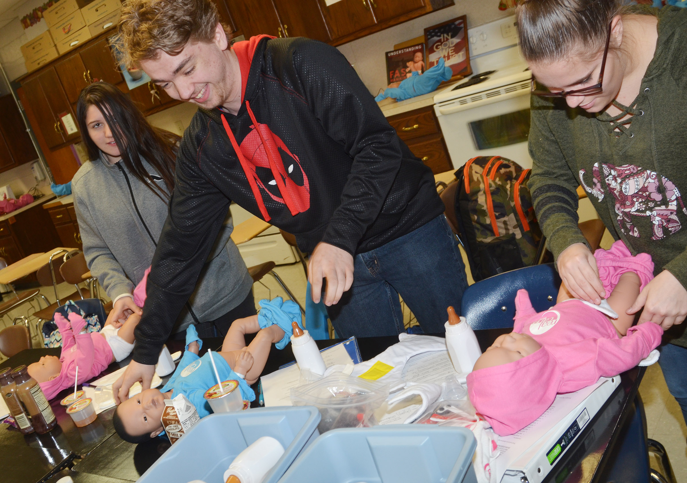 From left, CHS freshman Paula Hoskins and sophomores Anthony Shipione and Nevaeh Underwood change their Real Care babies.