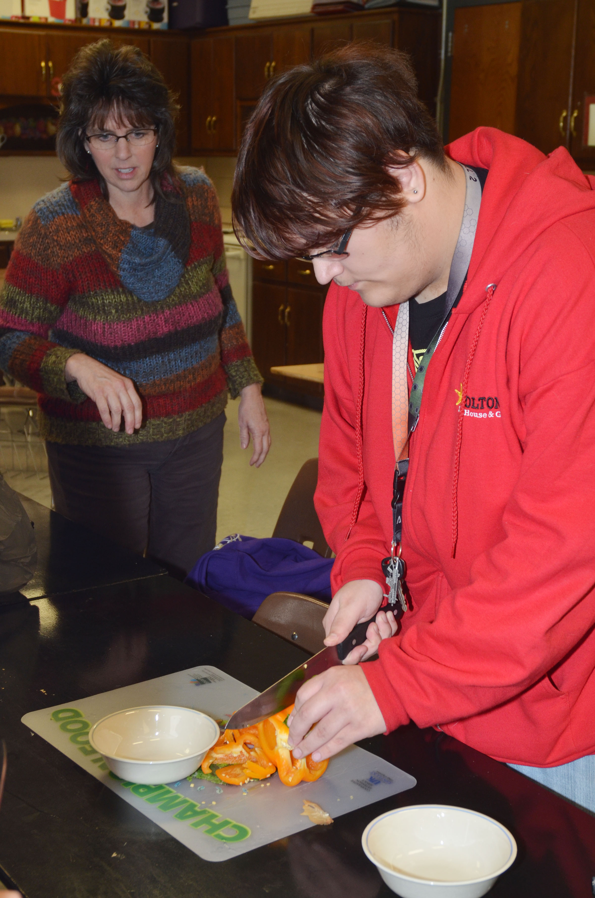 CHS teacher Deanna Campbell helps junior Aidan McMahan chop peppers.