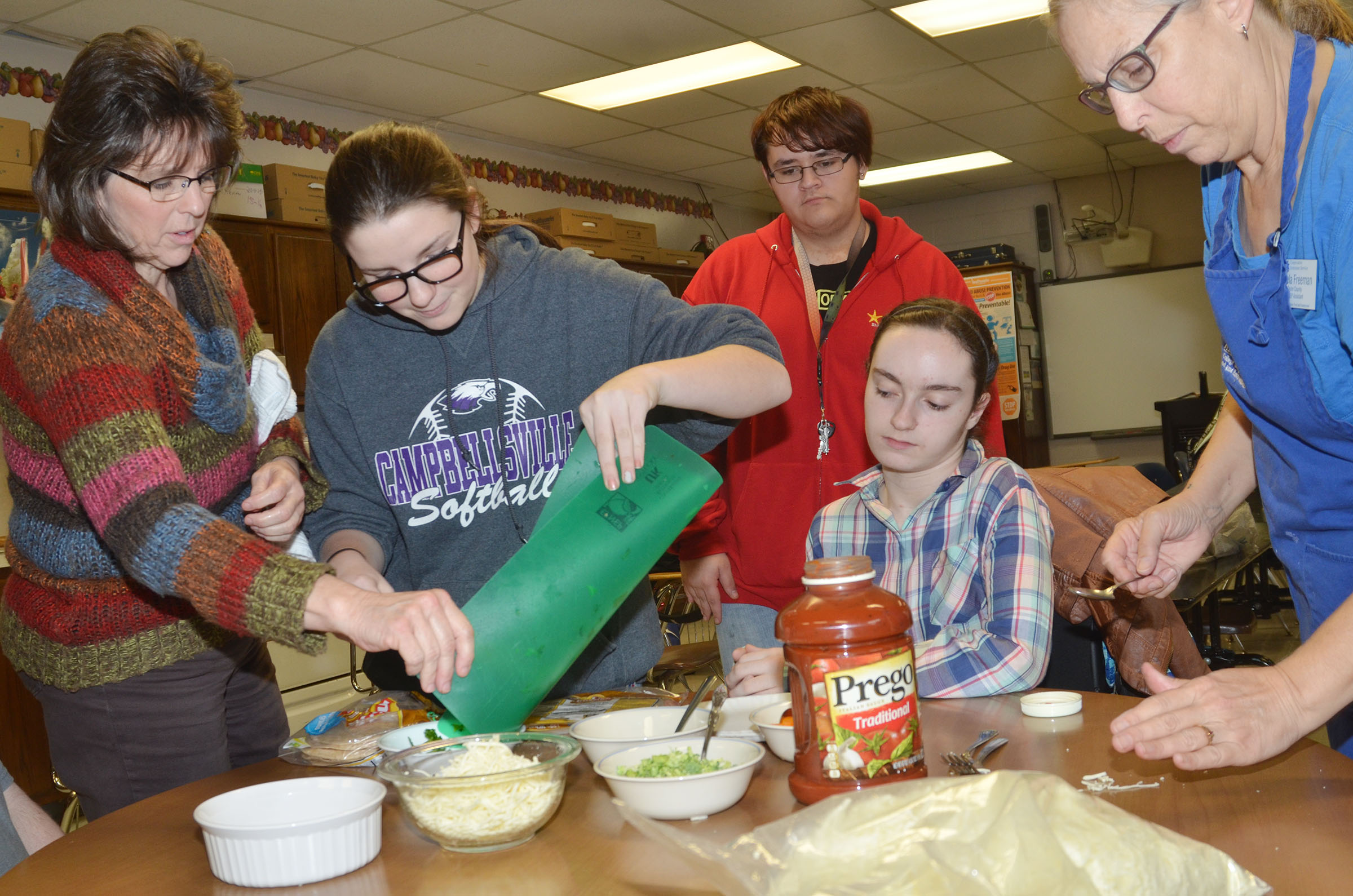 CHS teacher Deanna Campbell, at left, and Angie Freeman, expanded foods and nutrition program assistant at Taylor County Extension Office, at right, help students prepare ingredients for tortilla pizzas. From left are freshman Sydney Wilson, junior Aidan McMahan and freshman Jewell Cox.