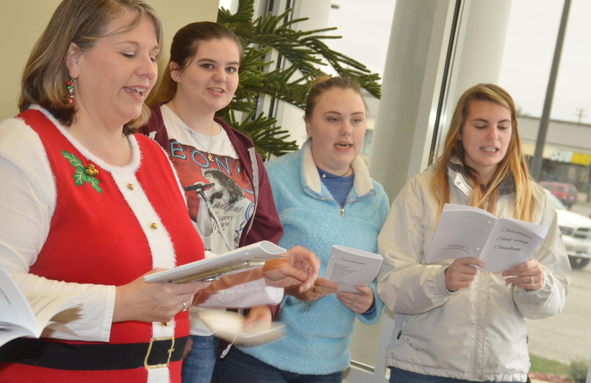 CHS choir members sing Christmas carols at Taylor County Bank. From left are music teacher Cyndi Chadwick and seniors Vivian Brown, Haley Fitch and Tiffany Kane.