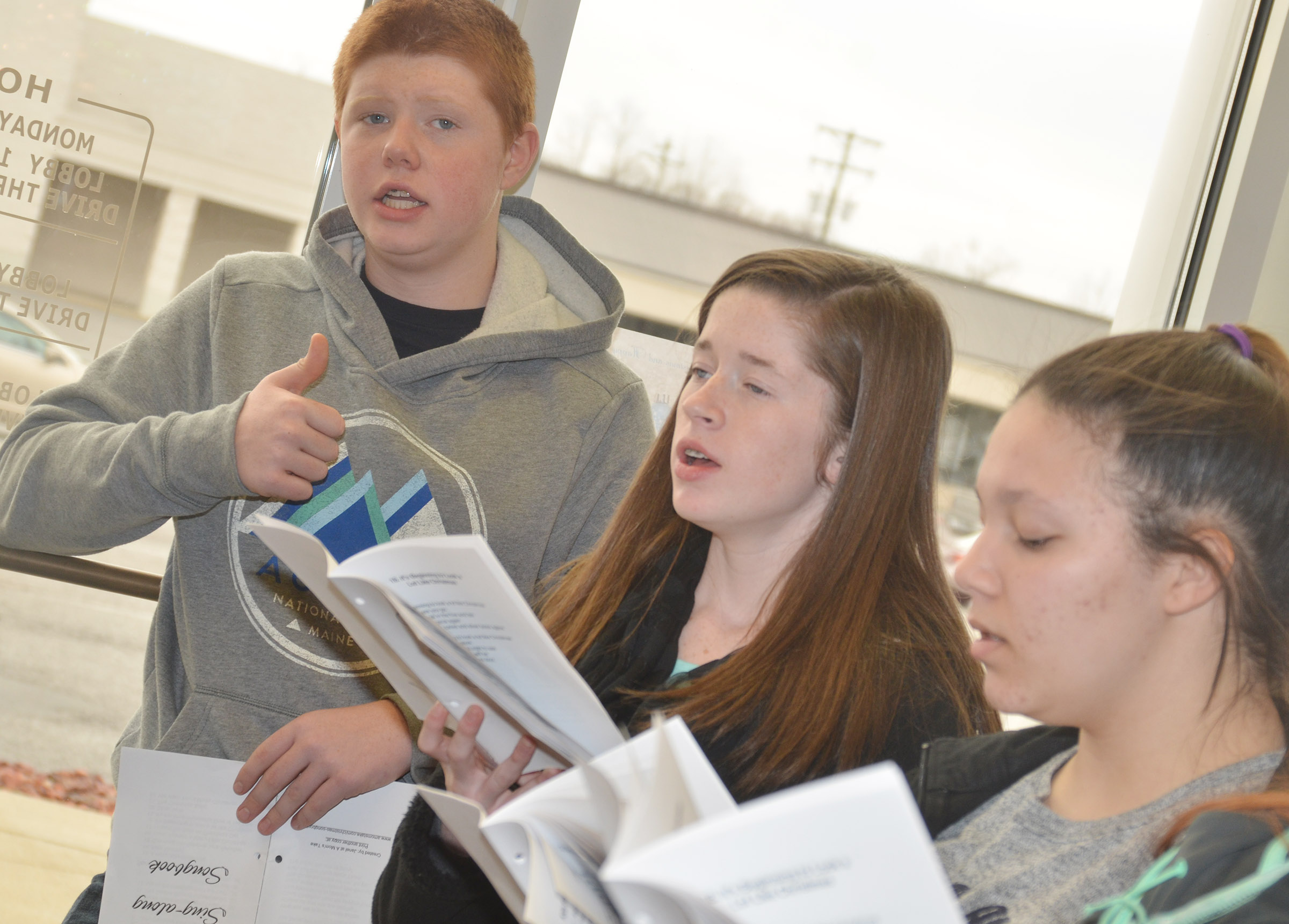 CHS choir members, from left, freshman Colin Harris, sophomore Gracyne Hash and freshman Tierra Bridgewater sing Christmas carols at Taylor County Bank.