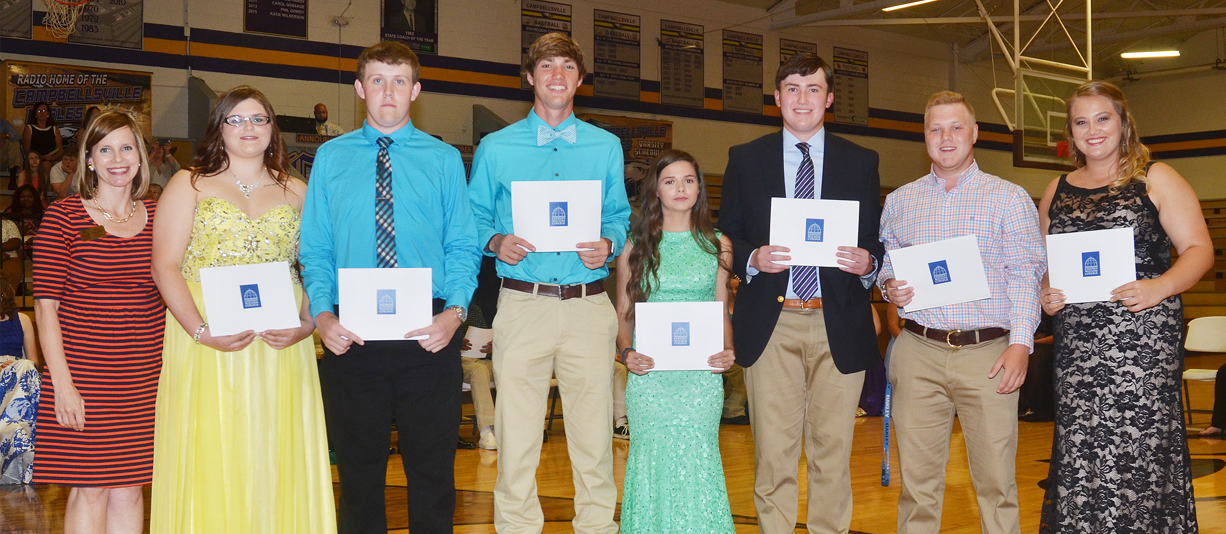 Receiving Lindsey Wilson College scholarships from admissions counselor Charity Ferguson, at left, are, from left, Vera Brown, Jared Brewster, Zack Bottoms, Shauna Jones, Zack Settle, Noah Wagers and Brenna Wethington.