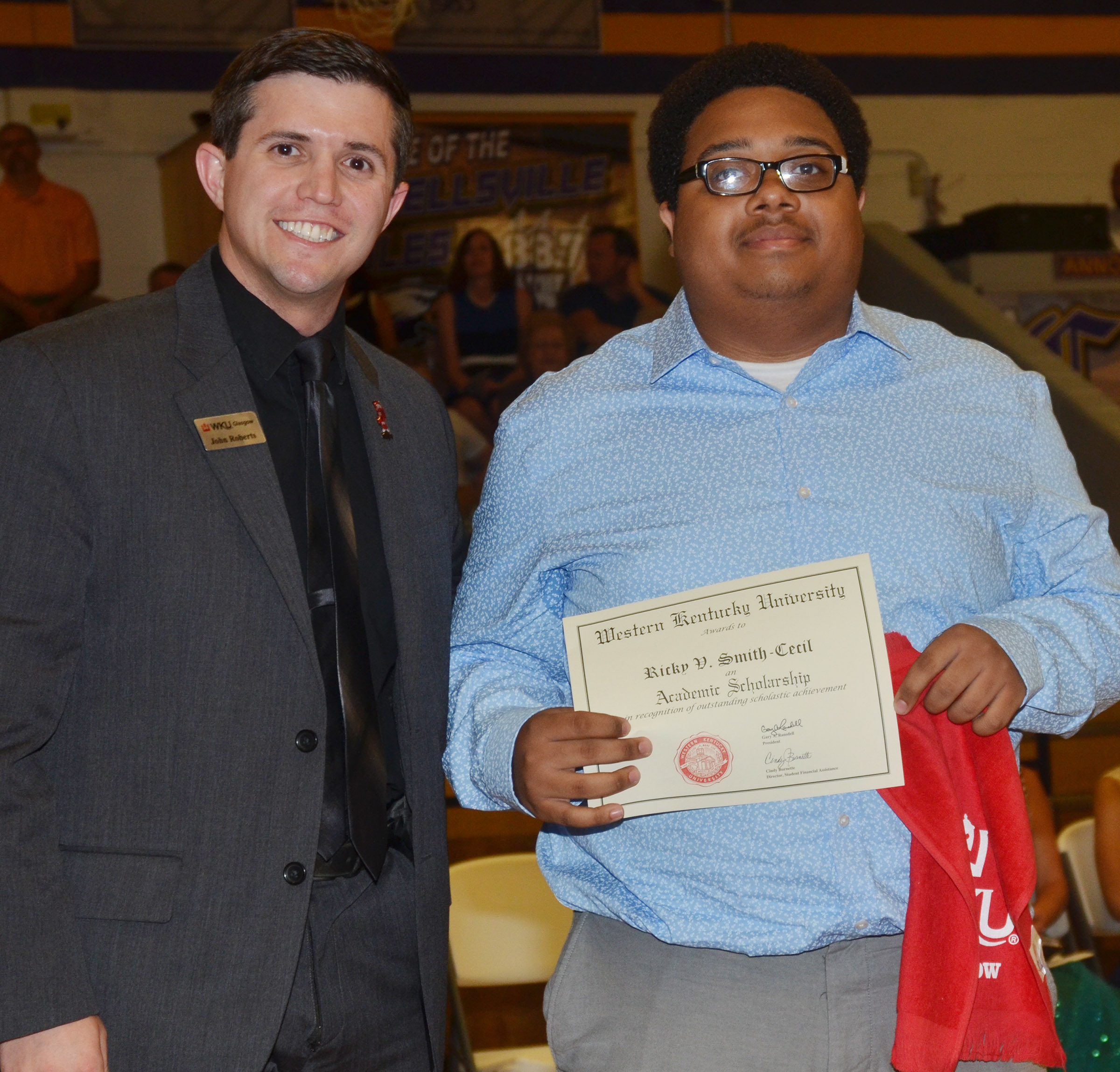 Ricky Smith-Cecil receives a scholarship from Western Kentucky University admissions counselor John Roberts.
