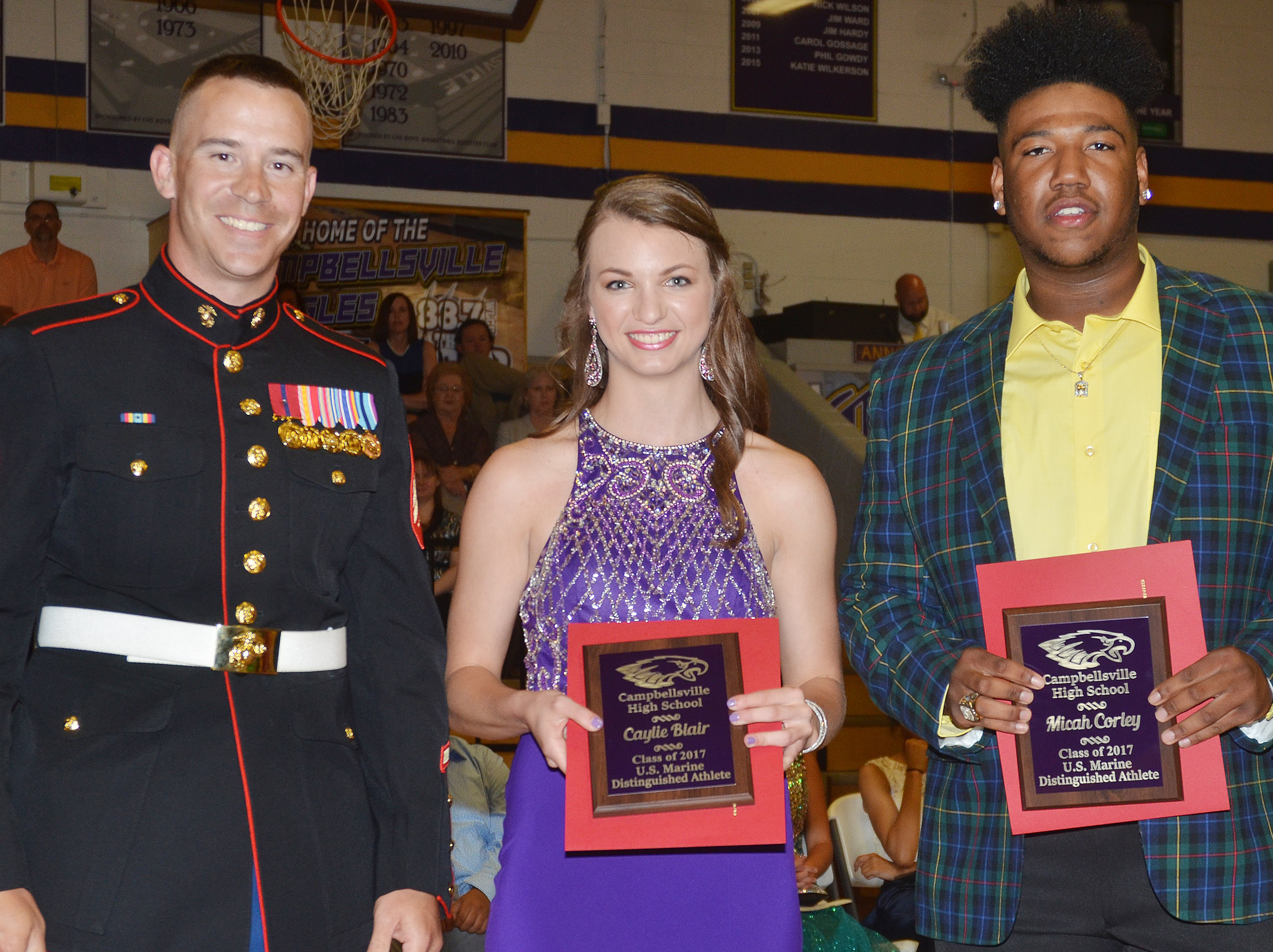 Caylie Blair and Micah Corley receive the U.S. Marine Distinguished Athlete awards from Sgt. Nelson.