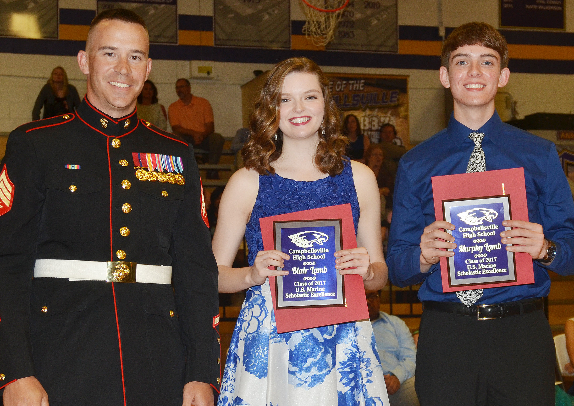 Blair Lamb and Murphy Lamb receive the U.S. Marine Scholastic Excellence awards from Sgt. Nelson.