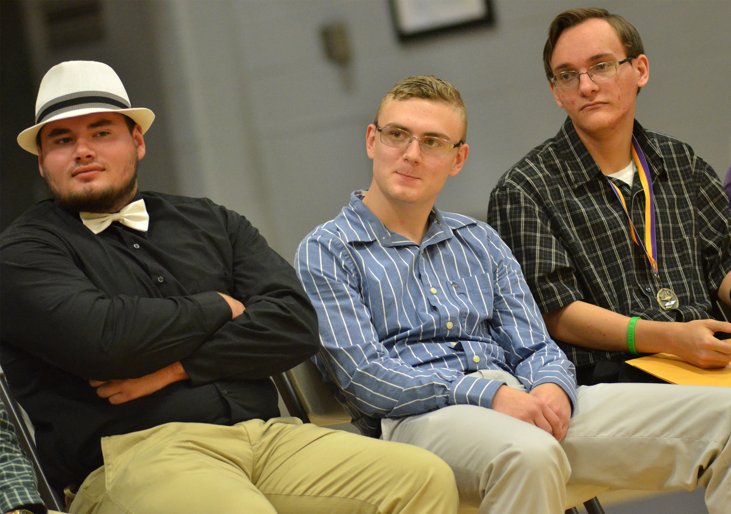 From left, Logan Brown, Ben Rafferty and Chase Atwood listen to the class history.