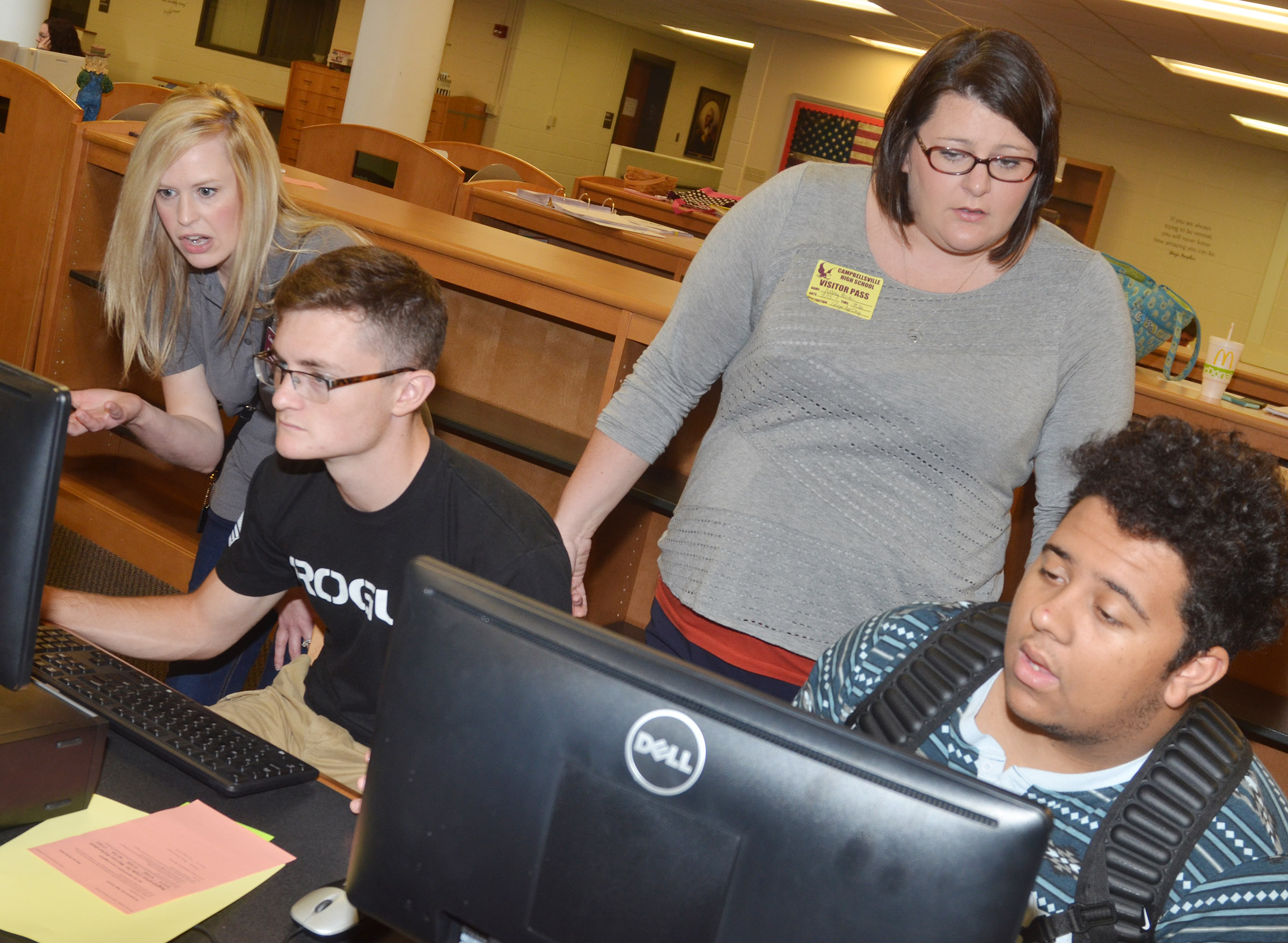 Campbellsville University Coordinator for Undergraduate Admissions Paula Caldwell, at left, and KHEAA representative Audrey Price help CHS seniors Bryce Richardson, at left, and Adrian Cravens apply to attend college.